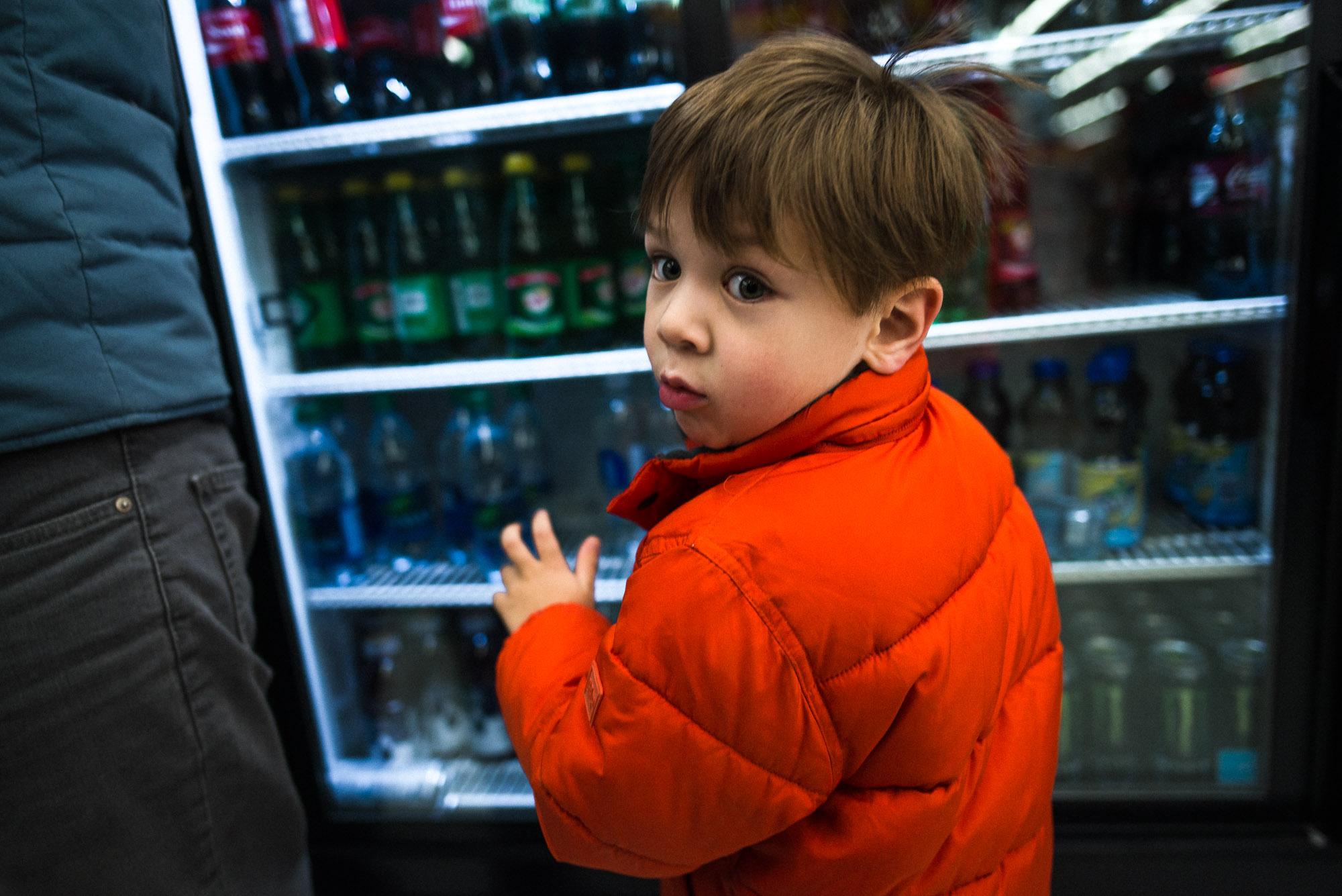 boy in orange coat looks back from a drink vending machine