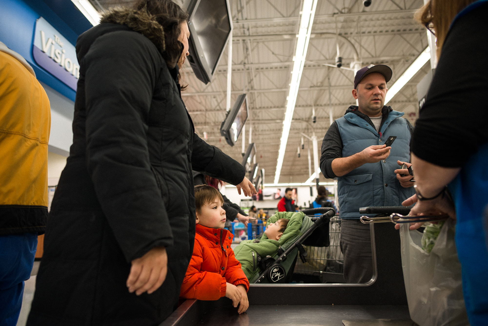 family stands at checkout counter