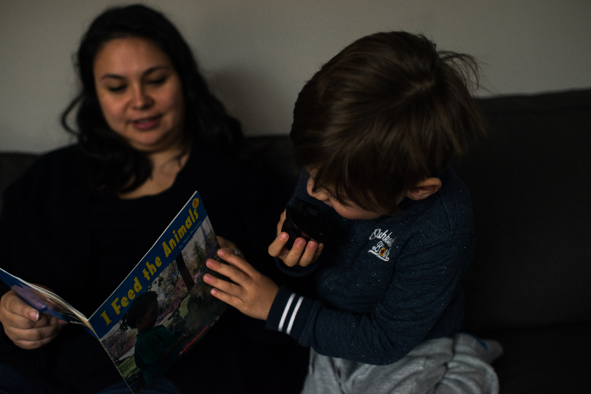 boy checks front page of book mom reads to him