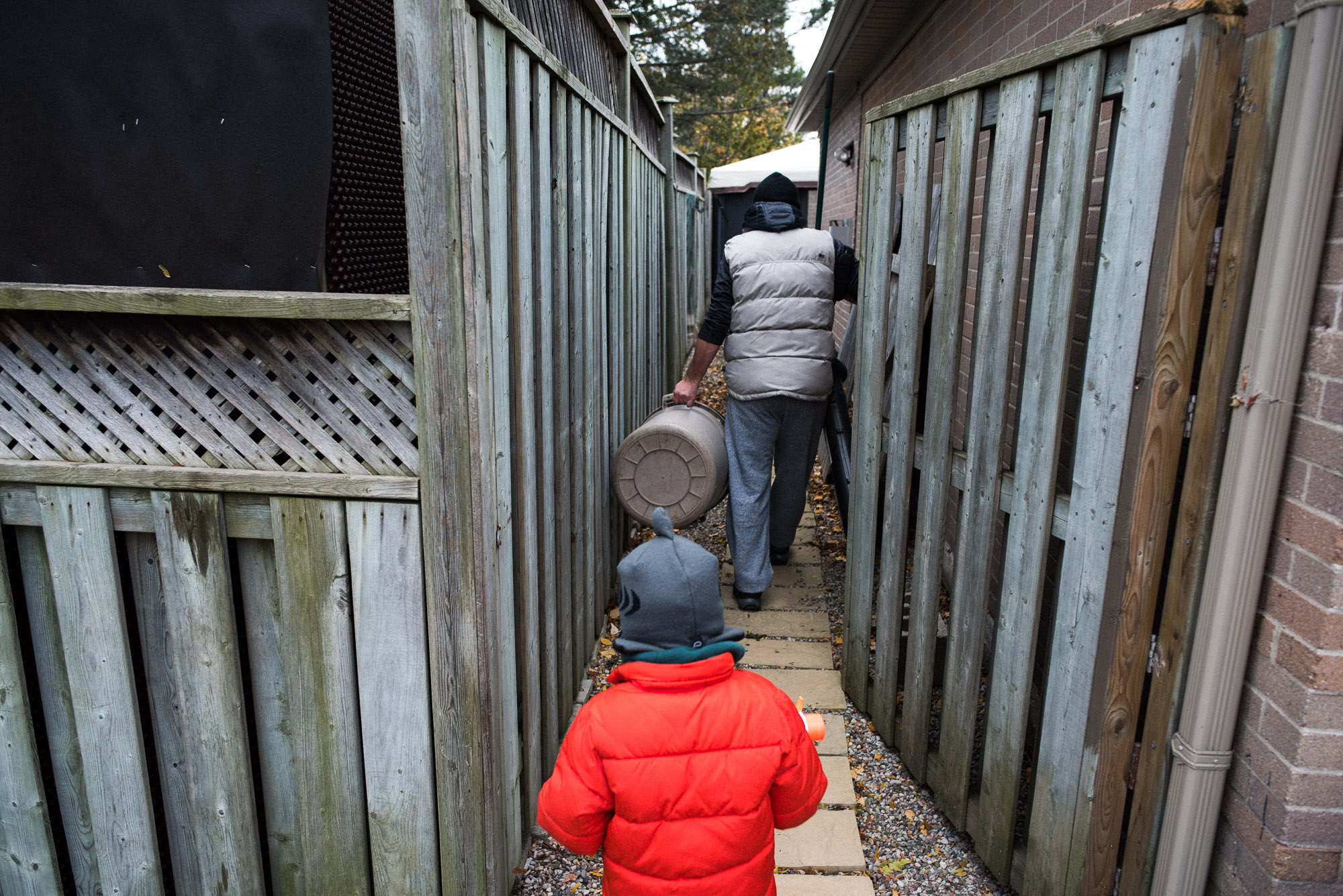 boy in orange coat follows dad to the back yard