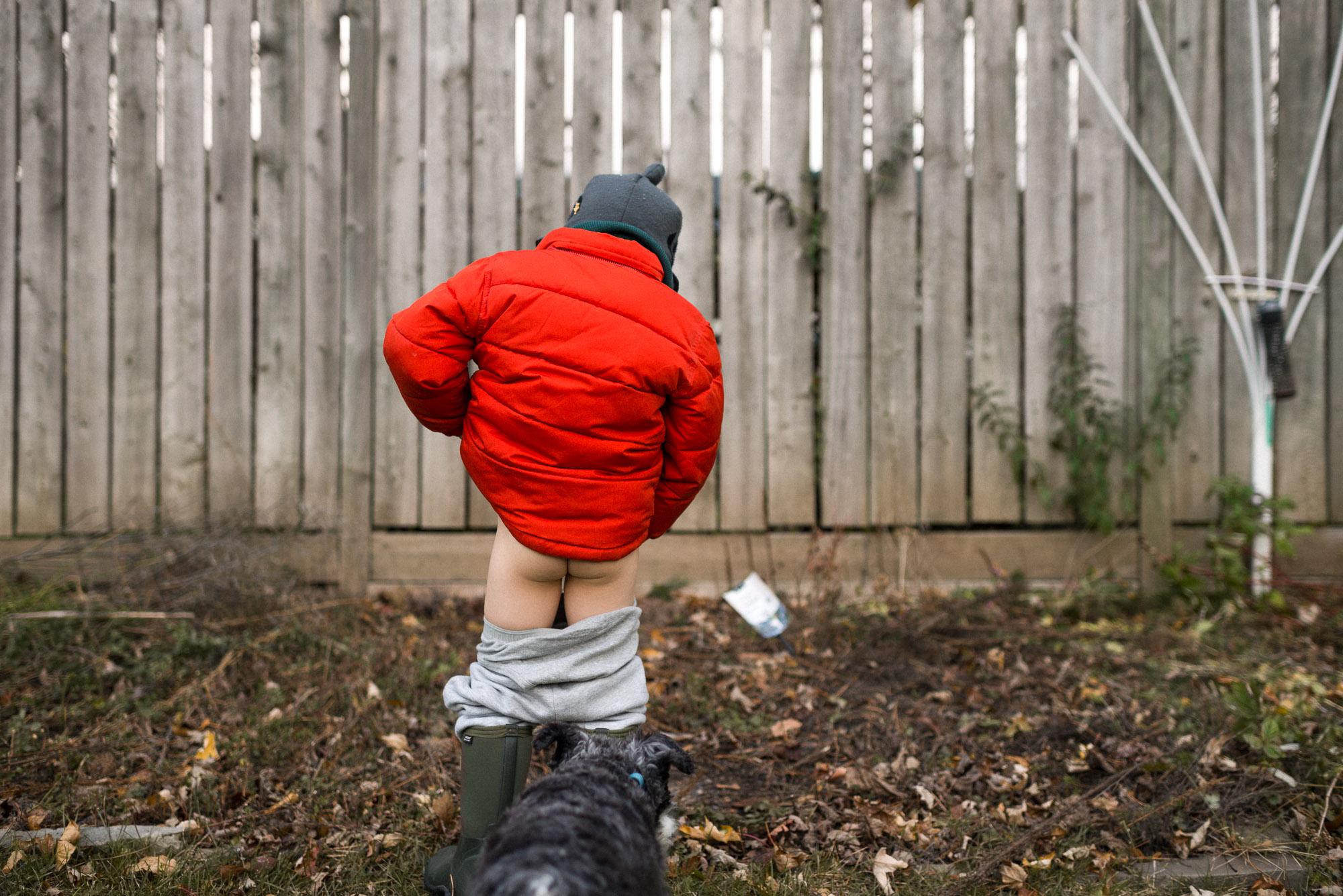 boy in orange coat pees outside