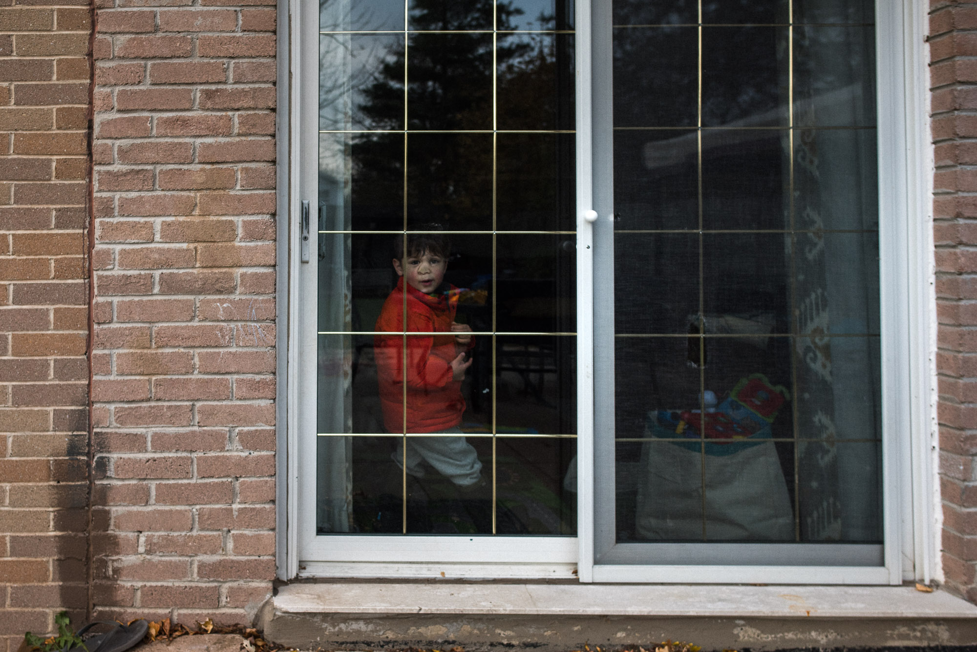 boy scrunches nose against patio door looking out