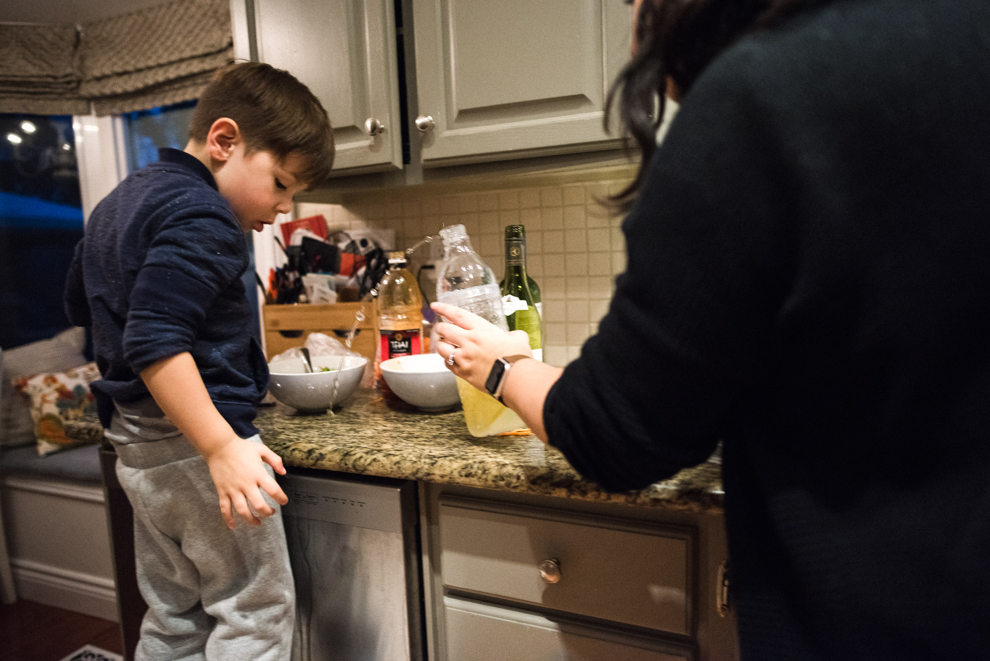 boy looks as mom catches spilling bottle in kitchen