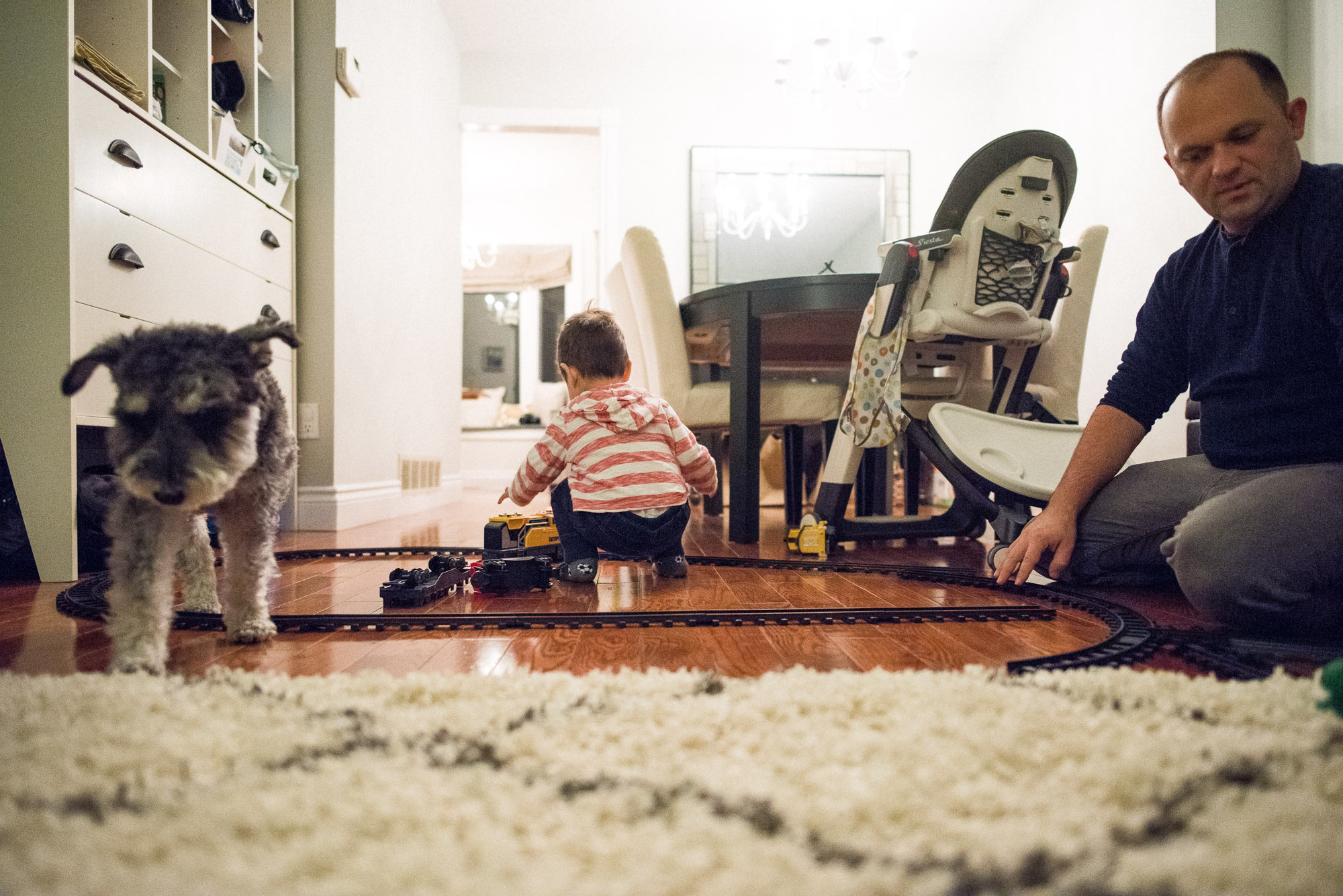 dad toddler and dog in the room with the toy train set