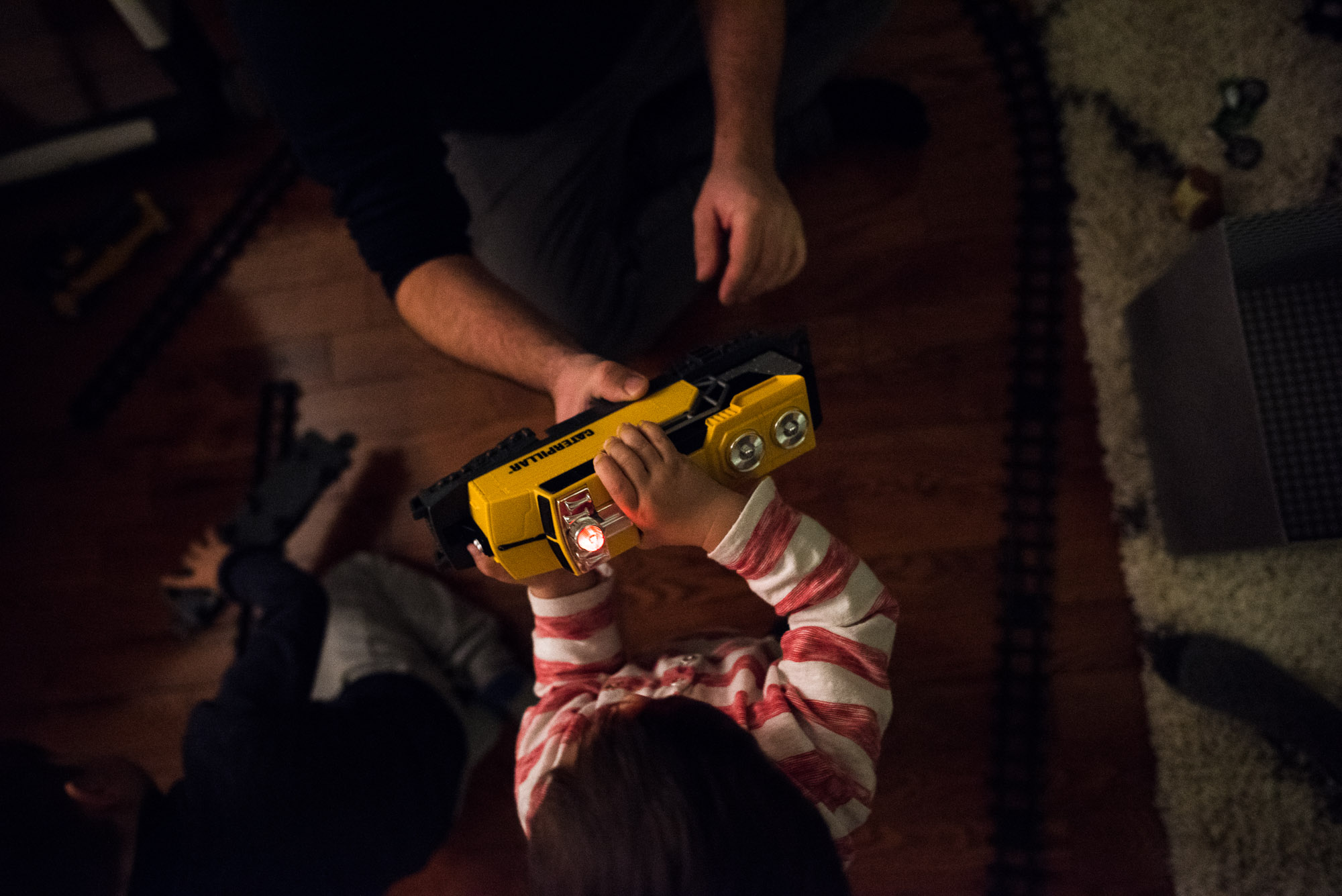 toddler and dad hold up a yellow toy train