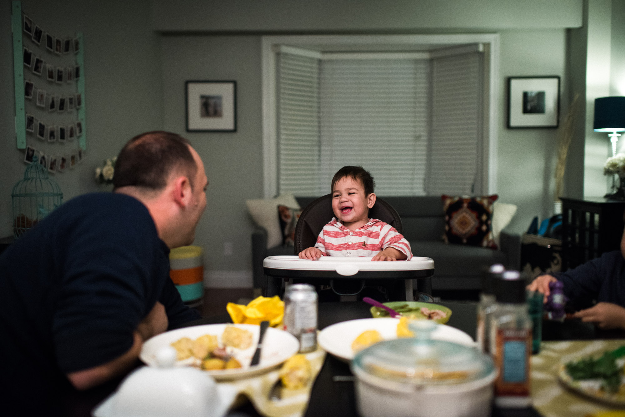 dad and toddler exchange smiles at dinnertable