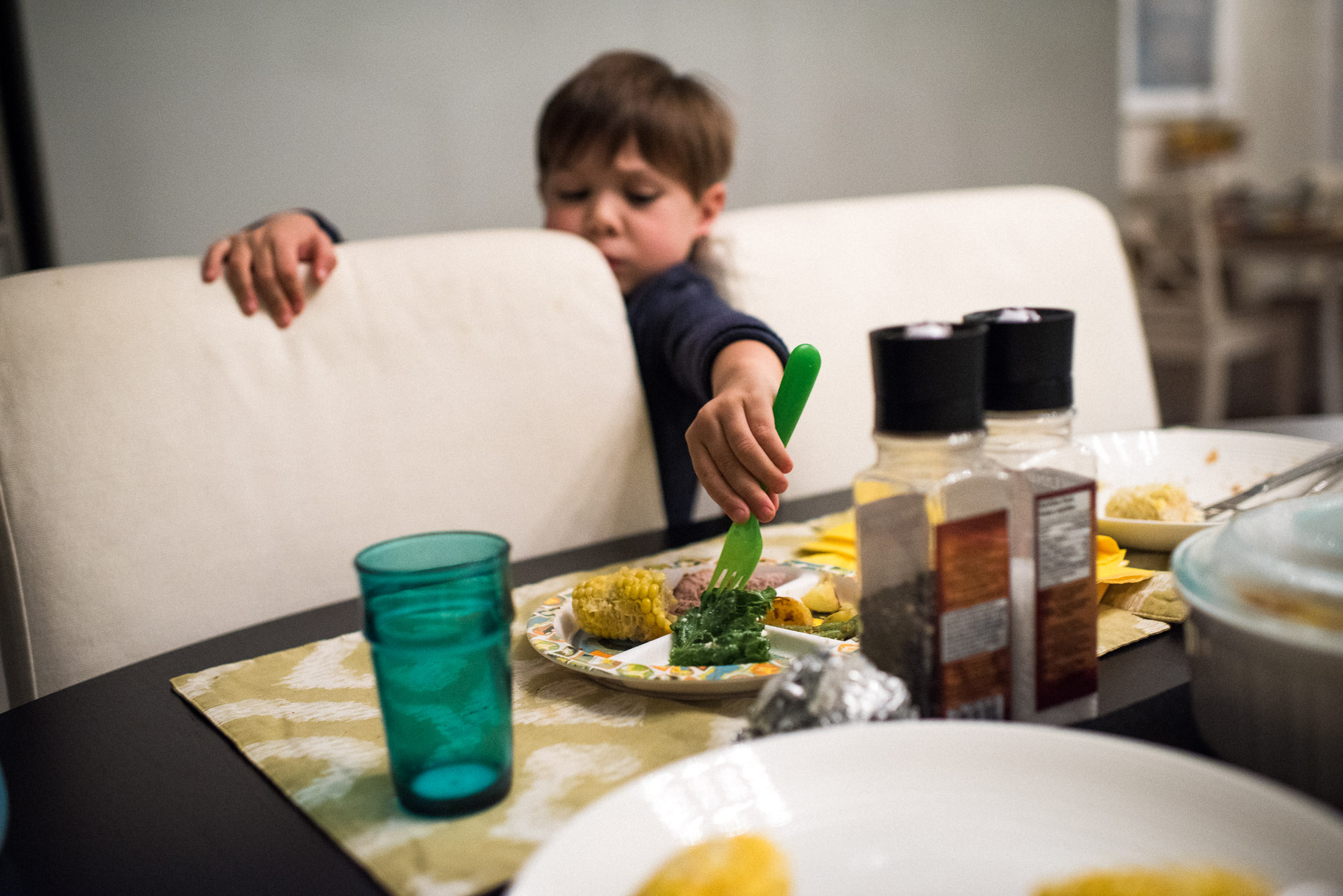 boy reaches between chairs to fork lettuce off a plate