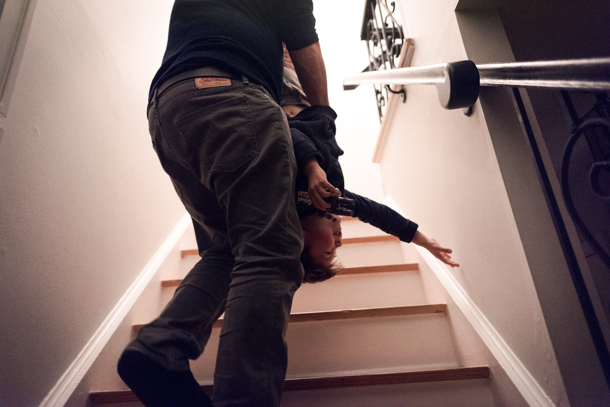 dad carries boy upside down upstairs