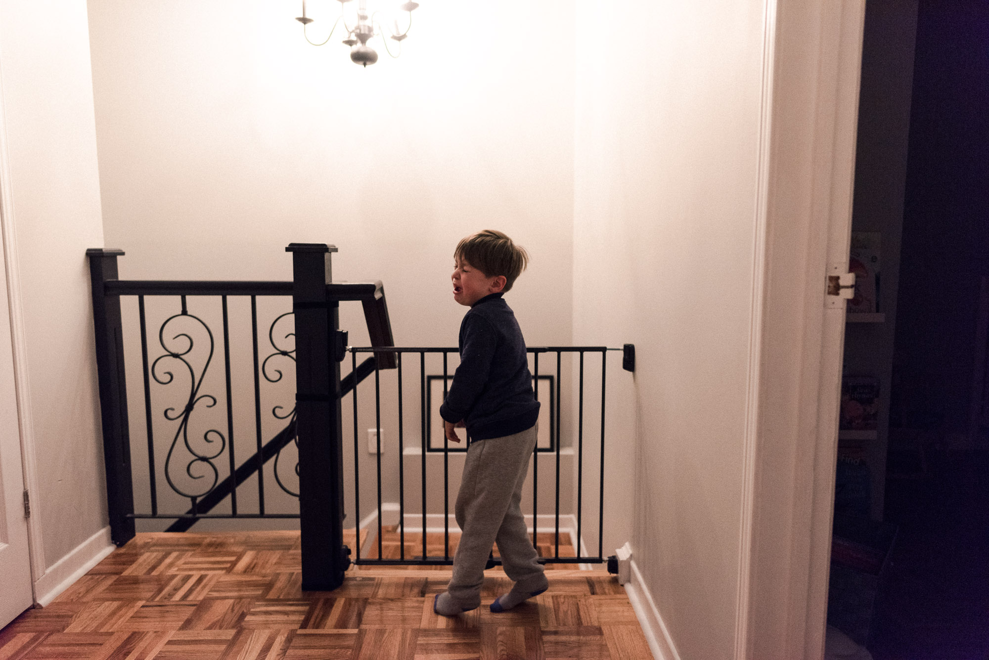 boy twirls, crying, at the top of the stairs