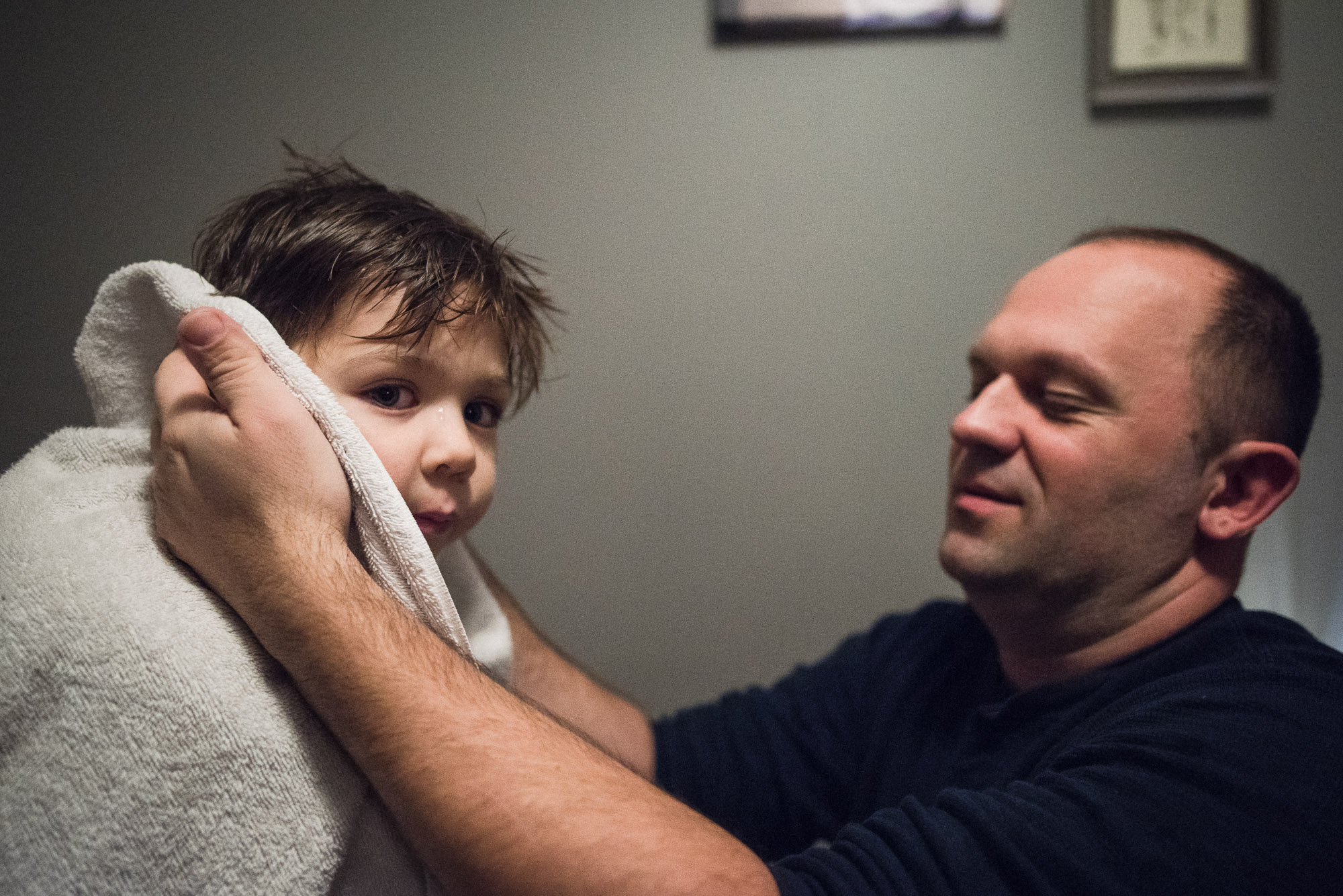 dad dries off boy's ears with a towel