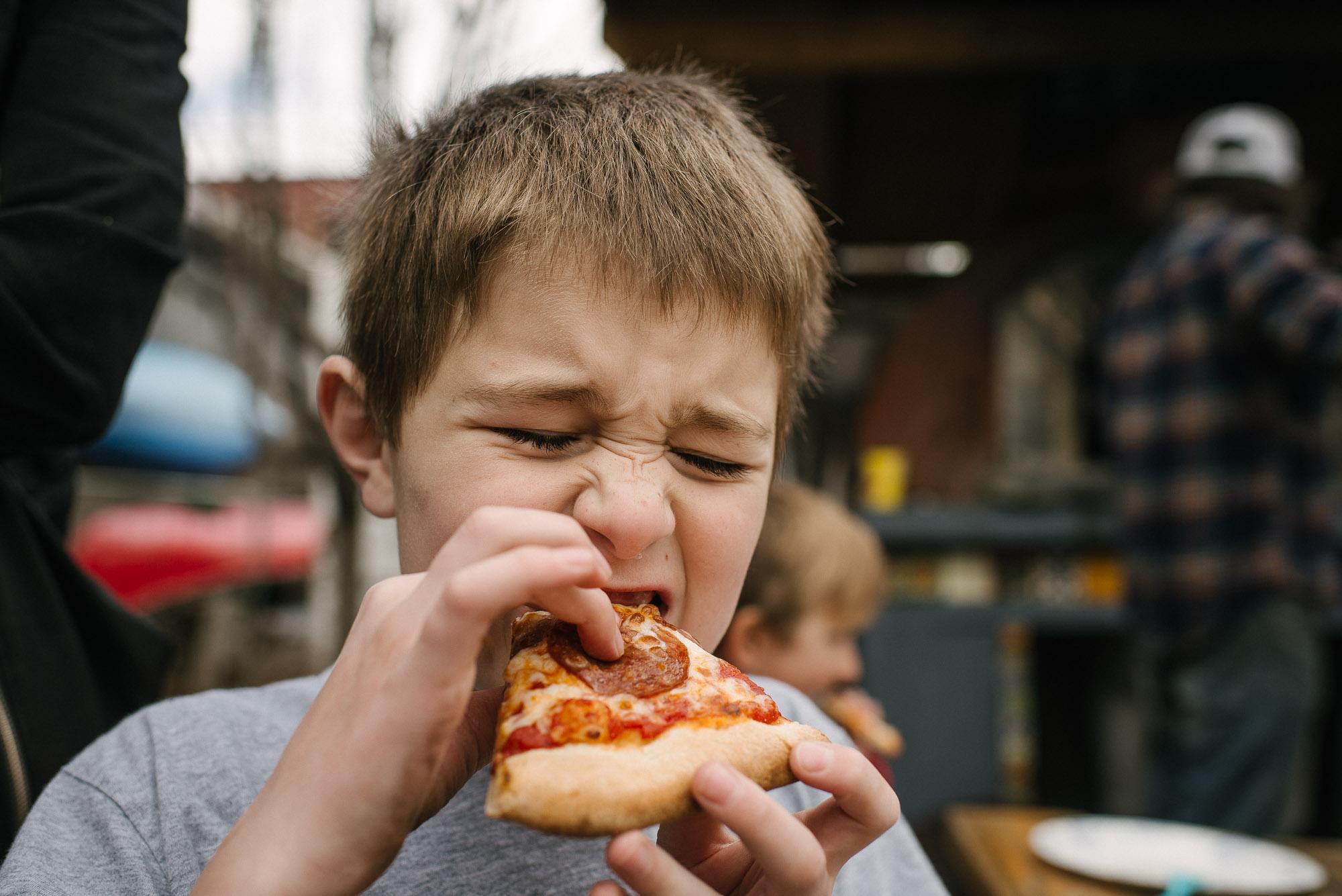 boy eats pizza