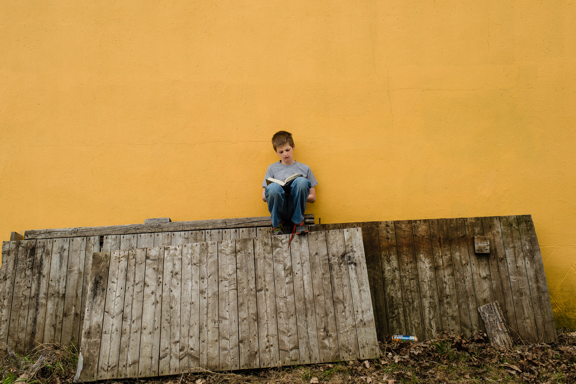 boy reads a book against a yellow wall