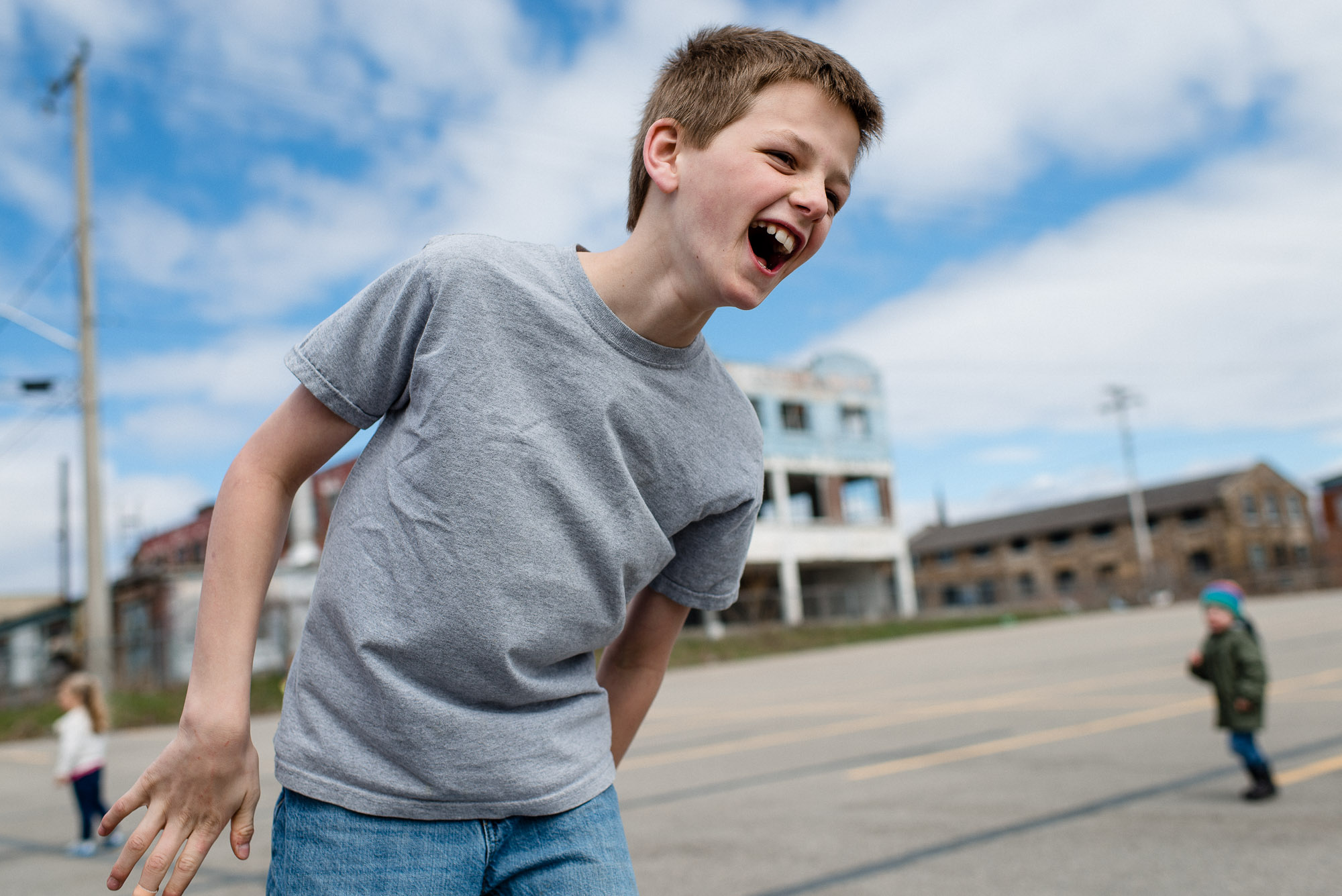boy laughs against a blue sky with clouds