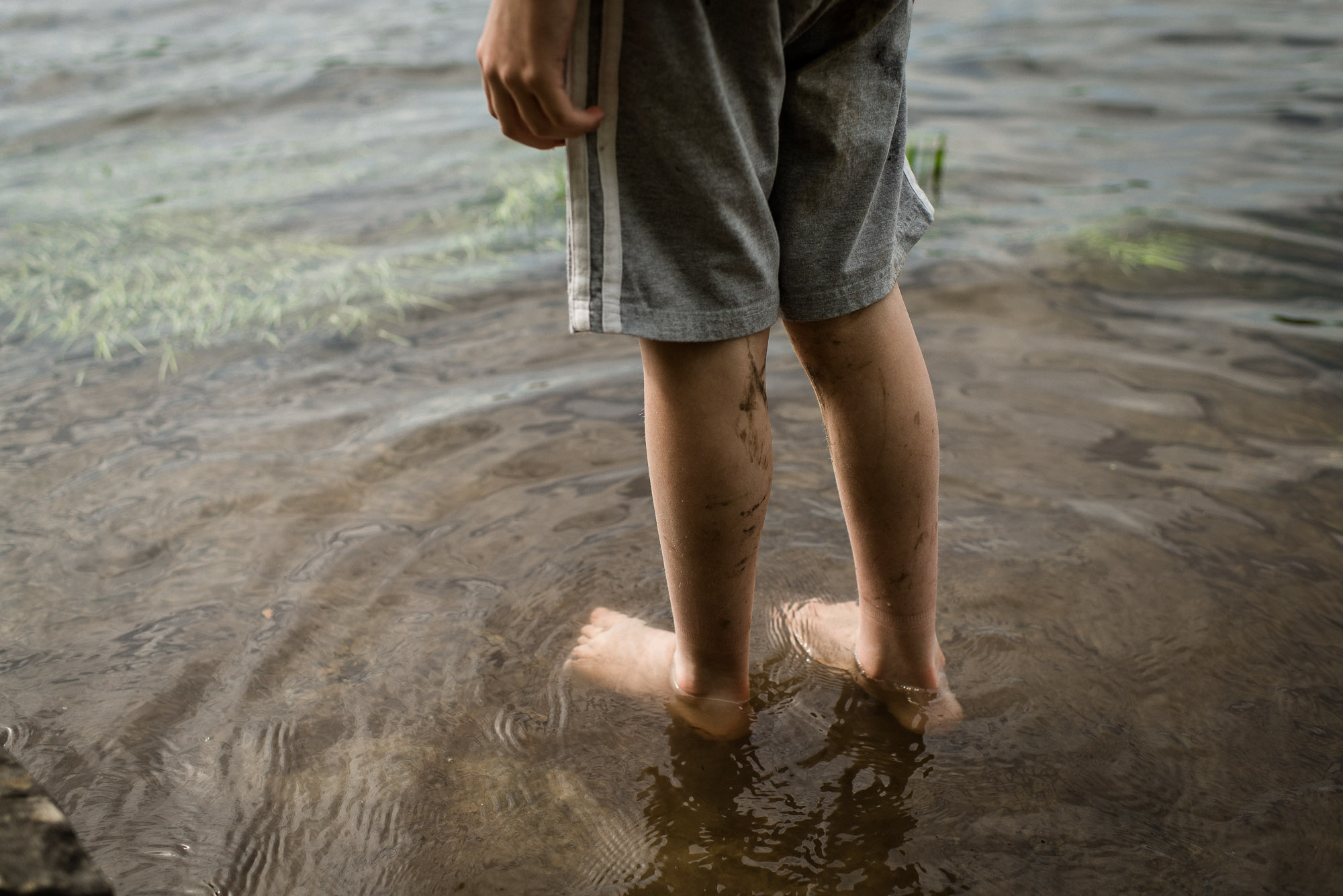 boy's legs wading into lake waters