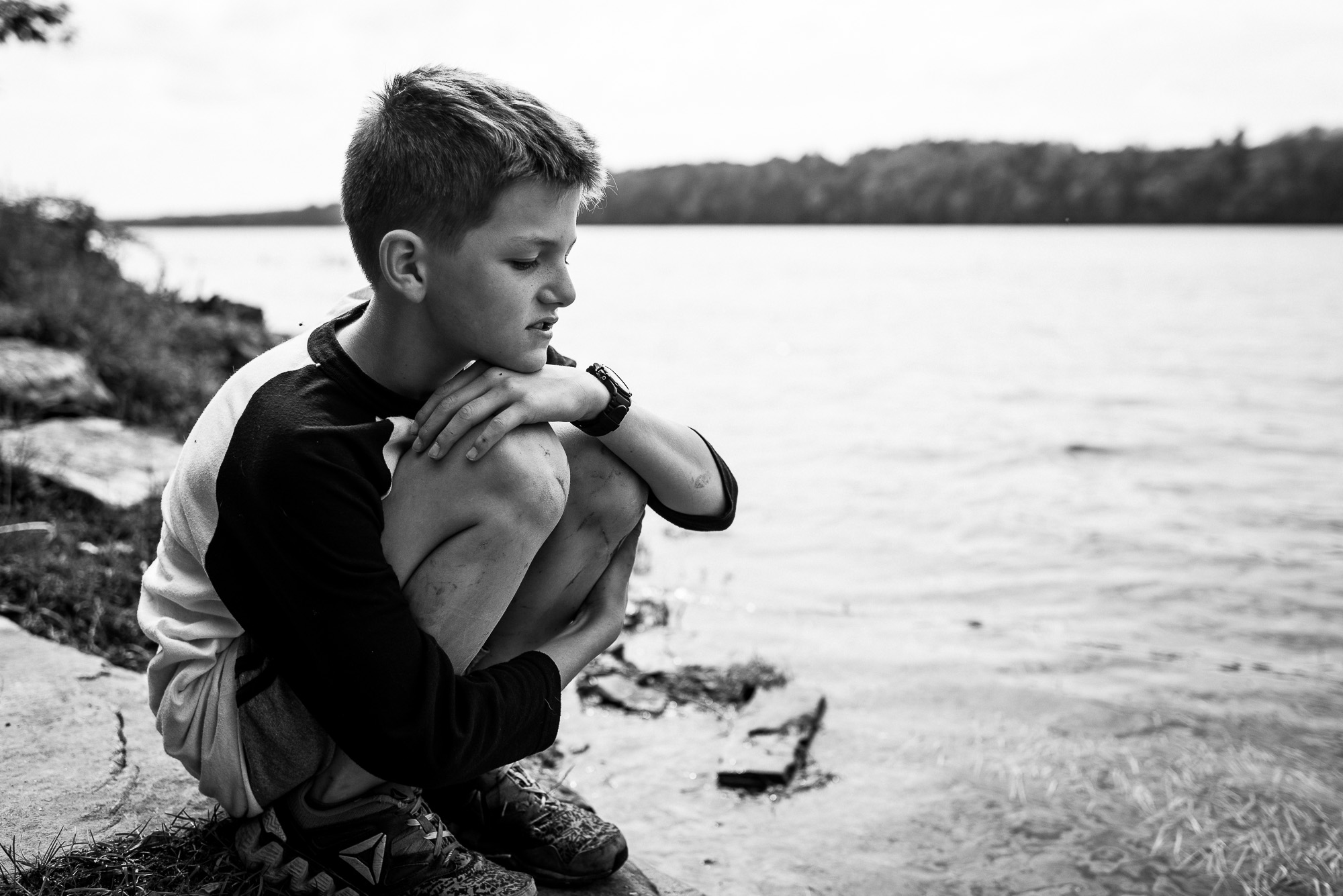 boys sits on shore of lake
