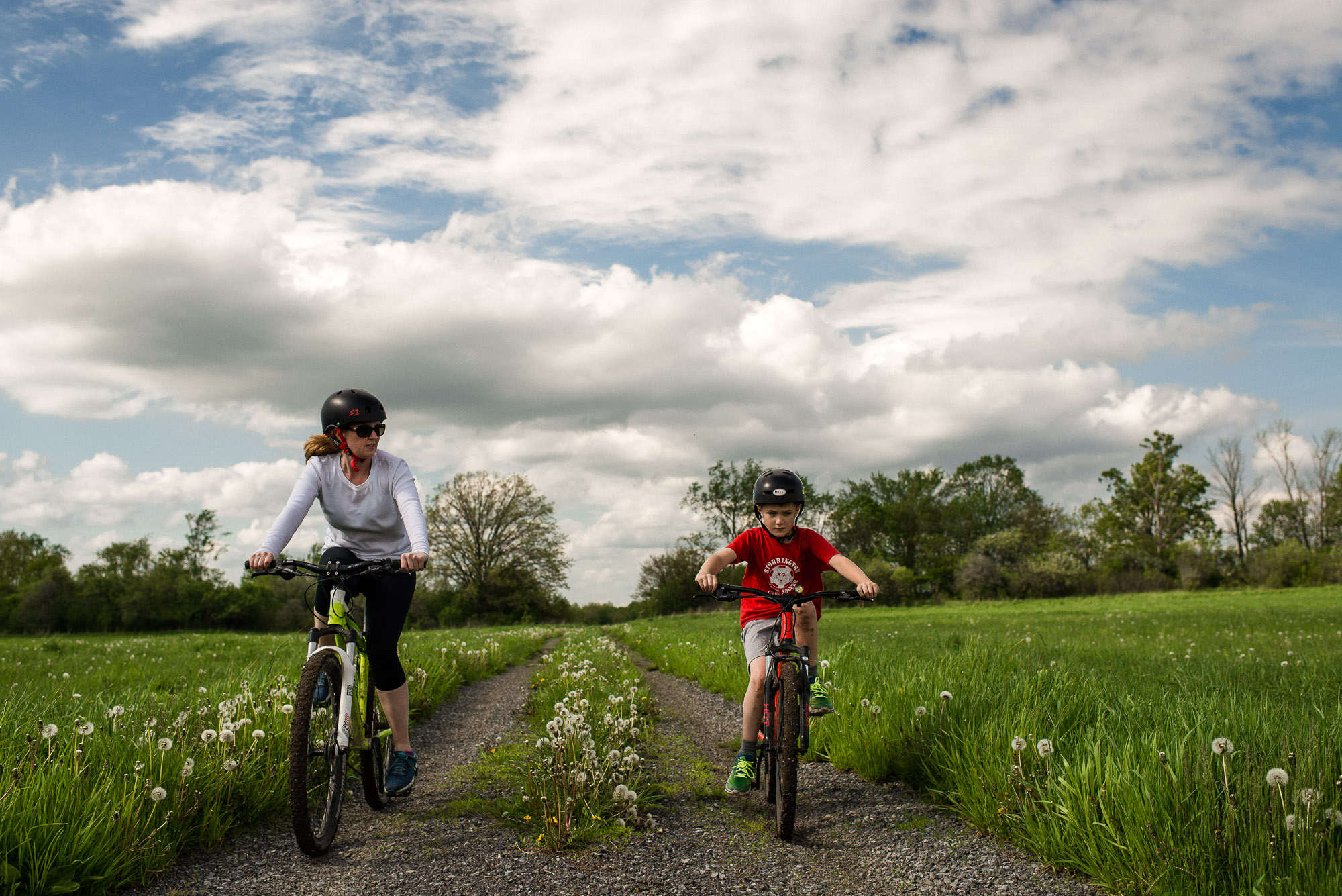 mother and son ride bikes through green field