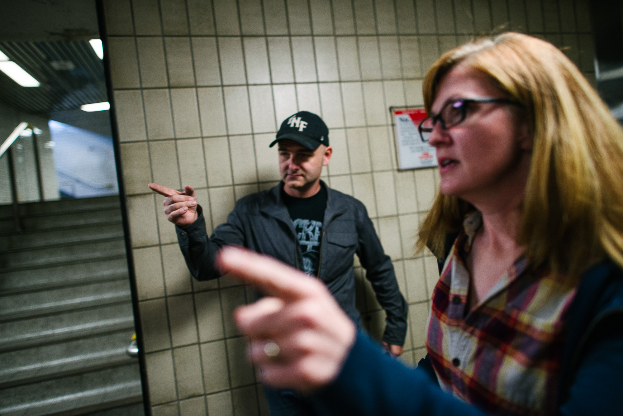 man and woman point in a subway tunnel