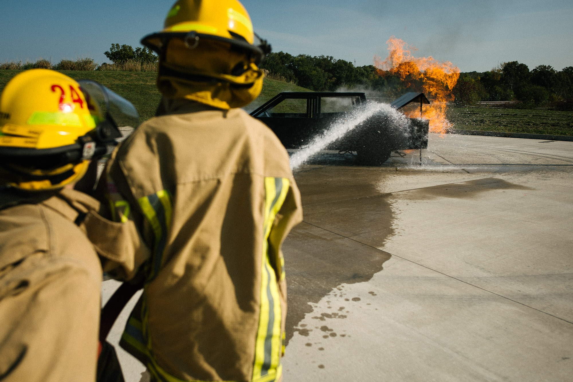 boys in fireman gear put out a mock fire on a training car