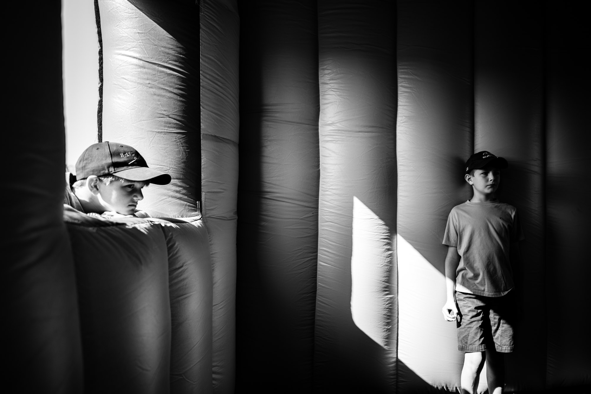 two boys stand around in shadows of a blow-up house