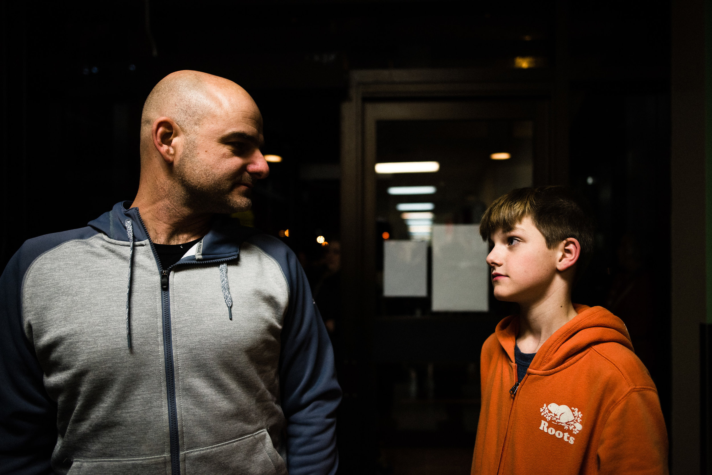 father and son look at each other under indoor lights