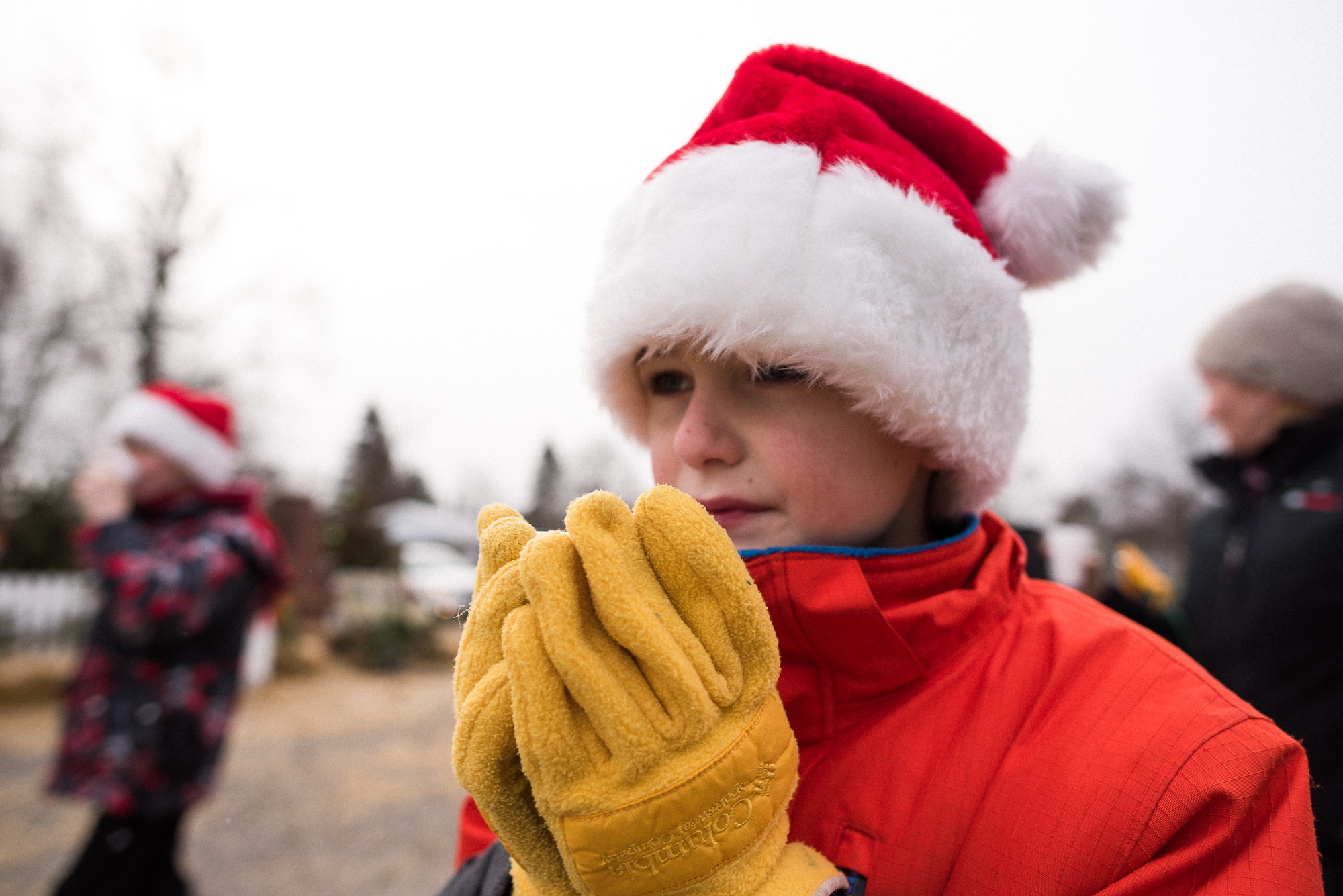 boy with Santa hat holds hot chocolate cut with yellow gloves