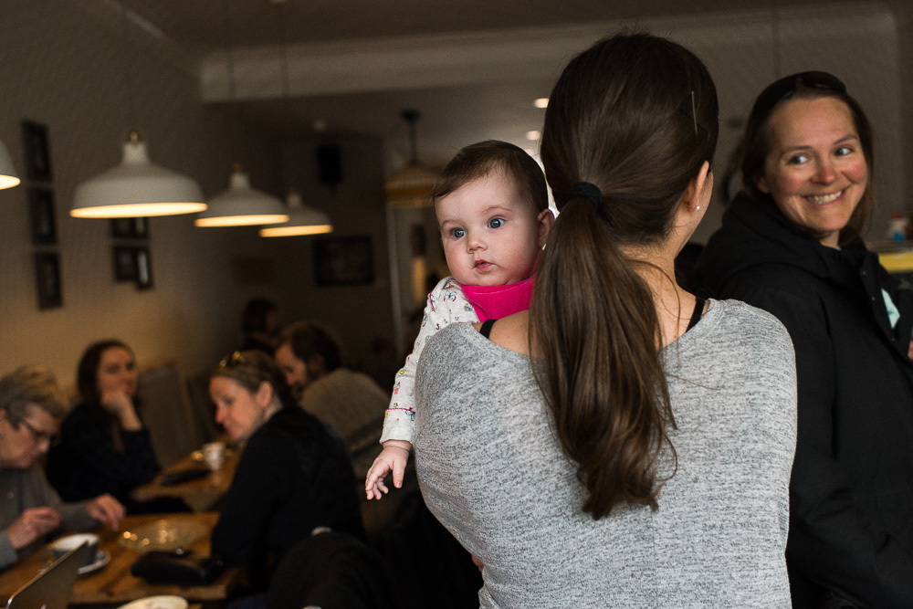 Logan carries her daughter and greets cafe patrons