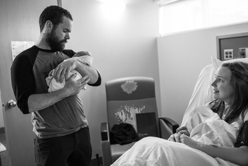 father holds newborn baby while mother watches on