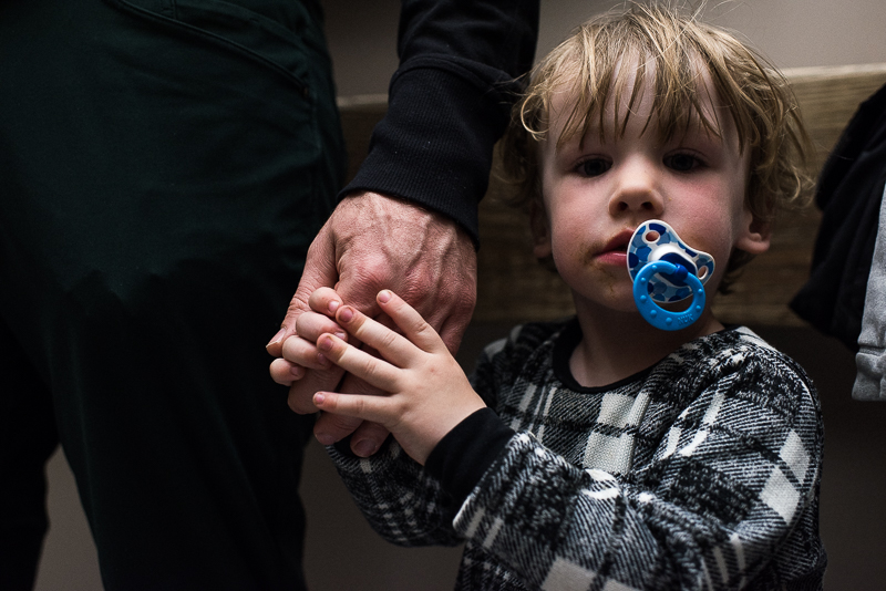 little boy with a soother clutches his father's hand
