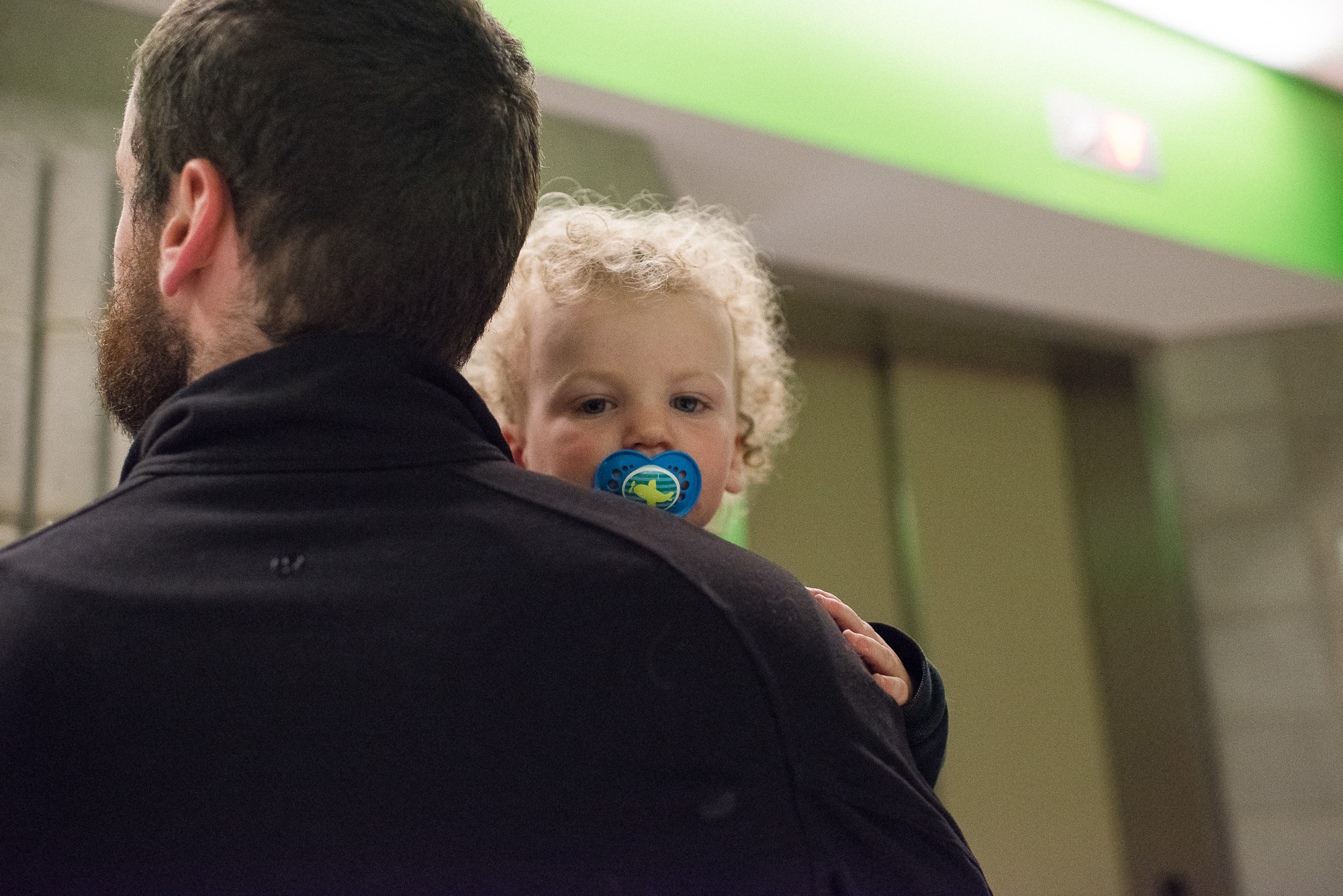 toddler is carried by his father in the elevator lobby