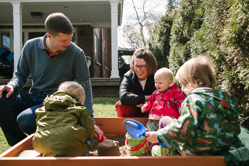 whole family plays near sandbox outside during family documentary family photography session