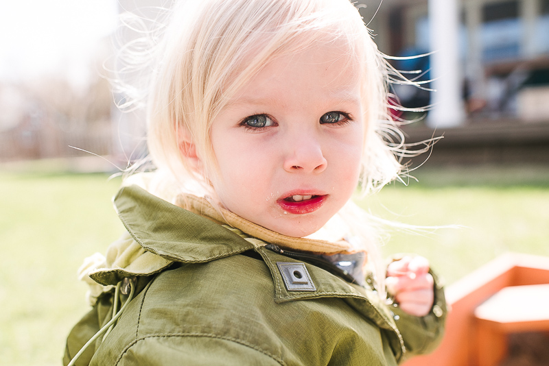 girl in green jacket looks at the camera in sunlight