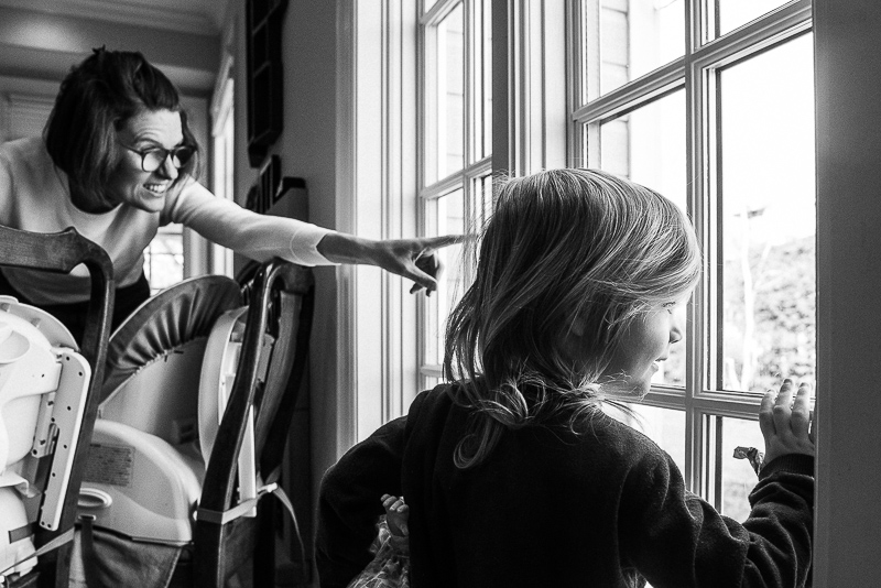 black and white photograph of mother and daughter looking outside the window during documentary family photography session in ottawa