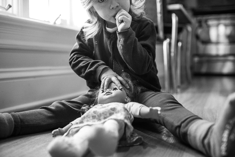 black and white photo of a girl with her doll during documentary family photography session in ottawa