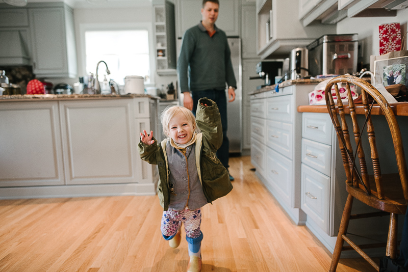 young girl in green jacket runs smiling in the kitchen during ottawa family photography session