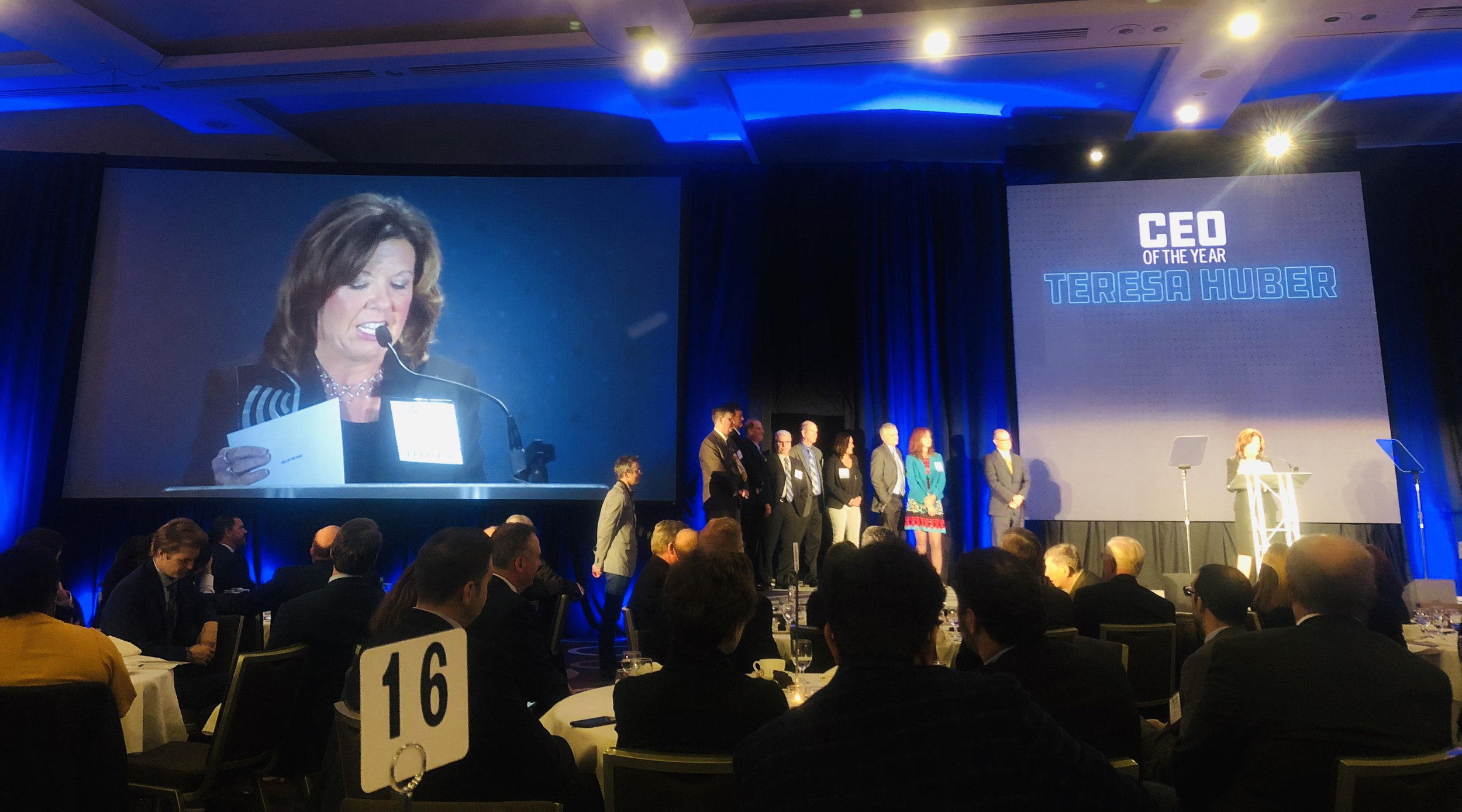 Joined onstage by several Intervala team members, Teresa Huber accepts her award as the 2018 CEO of the Year.