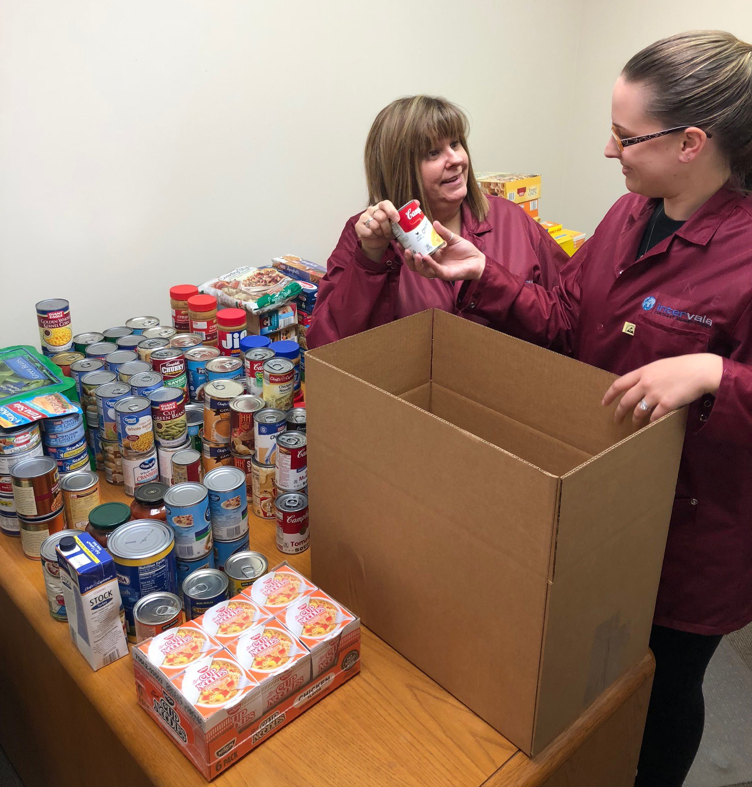 Intervala team members Toni Faulk and Courtney Shaffer pack up donated groceries for delivery to the food pantry.