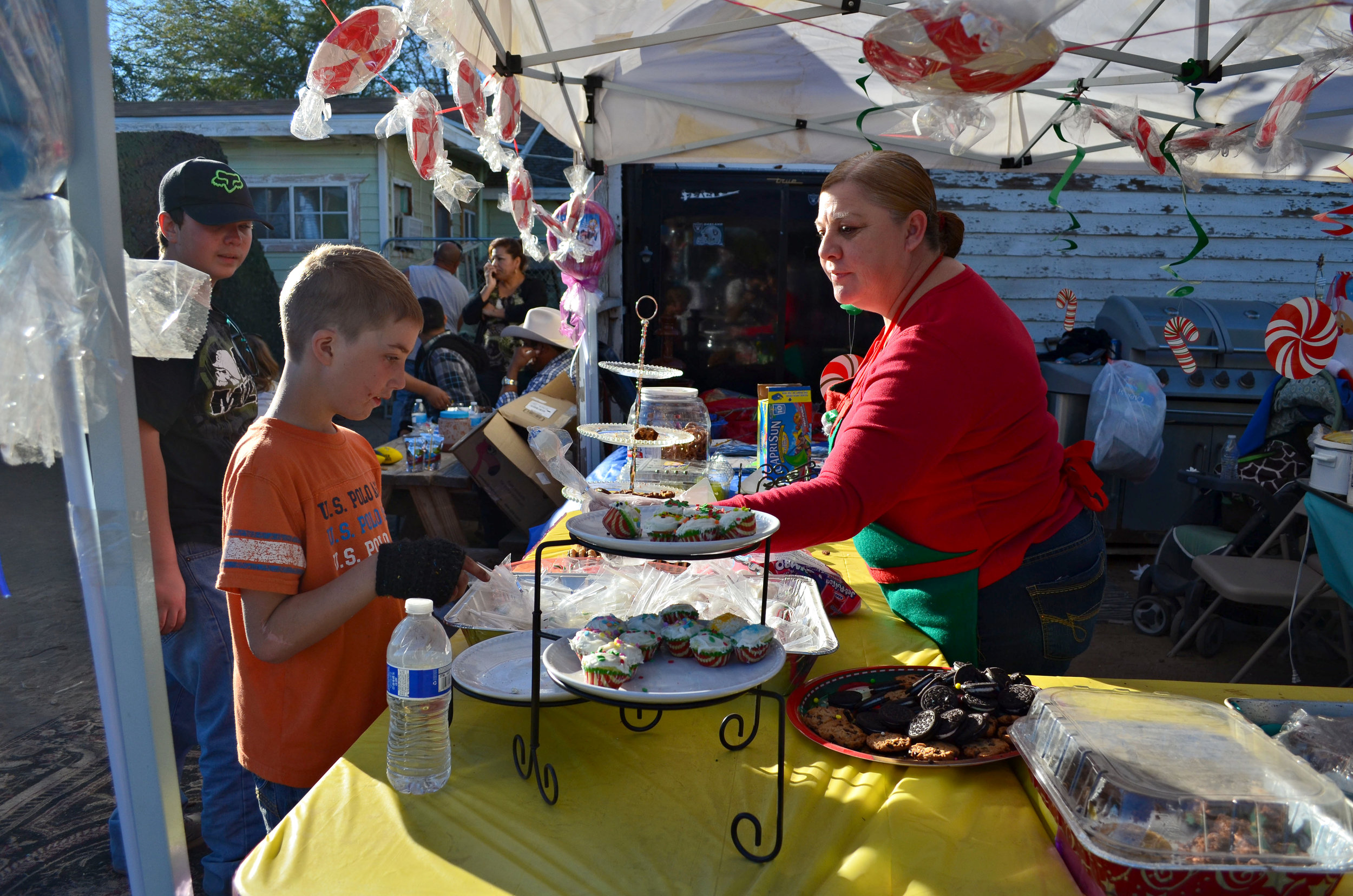 """Hope Verdugo gives Lucas Thayers, 8, a cake pop. Verdugo and her friends turned a corner of the Cardenas family's yard into """"Grandma's Gooey Sweet Shop for the Forgotten Angels Christmas party. (Imperial Valley Press/Antoine Abou-Diwan)"""