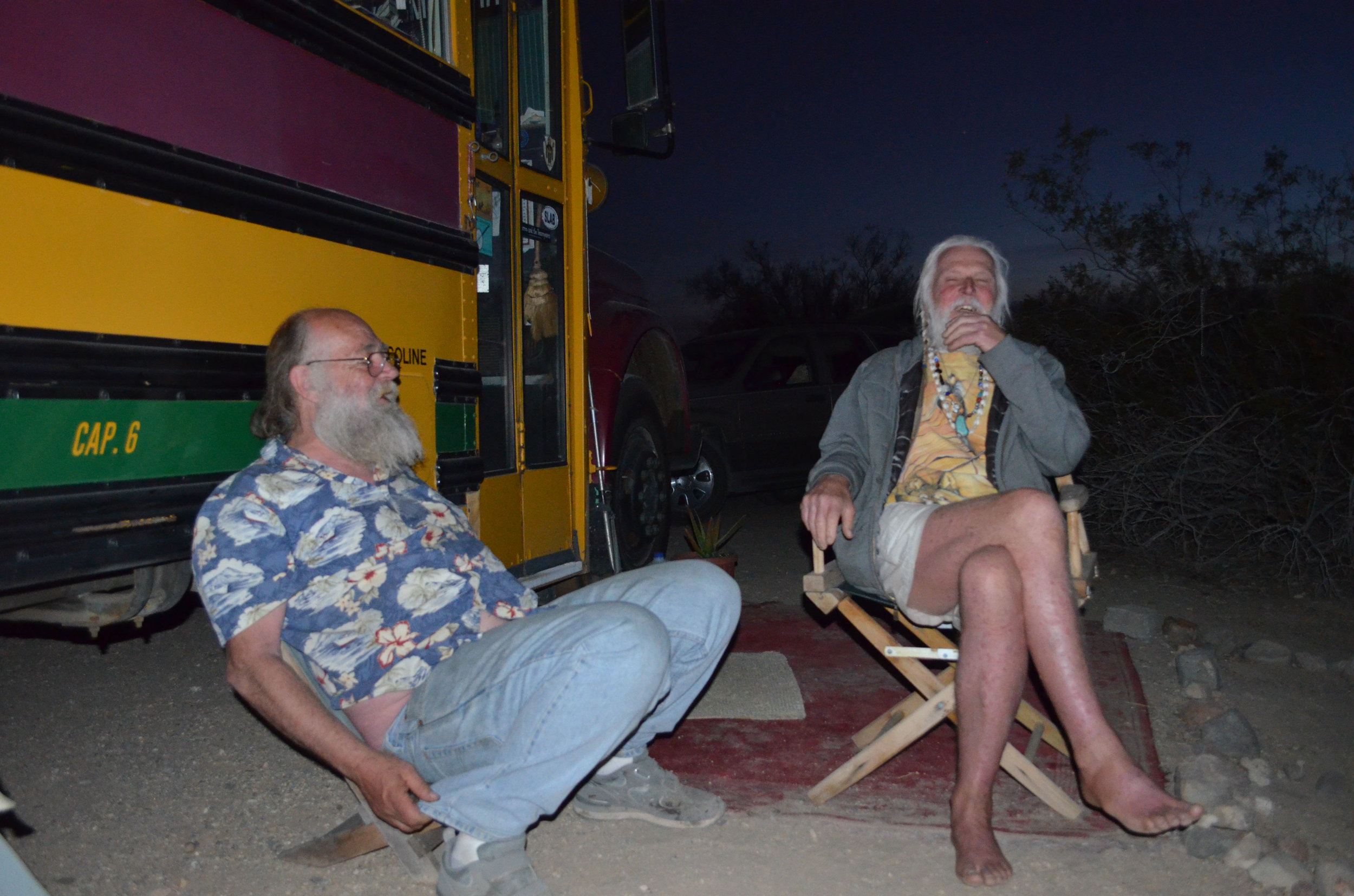 James Hoyle and Peter Lonnies hang out outside Lonnies' converted school bus. Both oppose efforts to change Slab City. (Imperial Valley Press/Antoine Abou-Diwan)