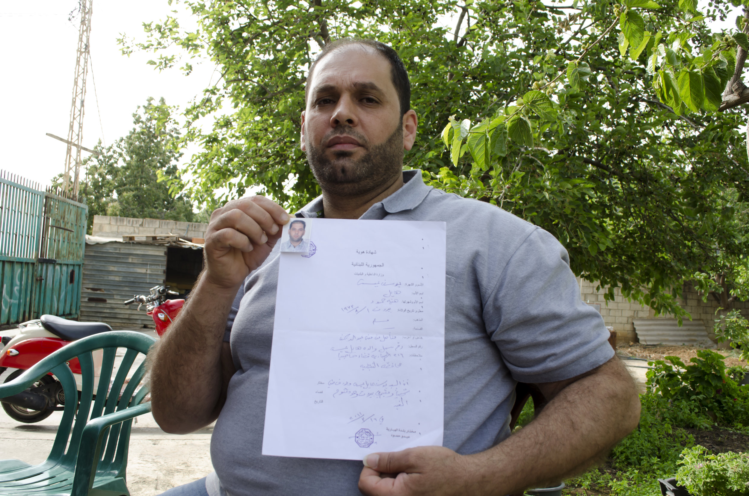 Youssef Issa shows a handwritten document from his village's mukhtar that attests to his identity and place of origin. But it is not proof of nationality in the eyes of the law.  (The Daily Star/Antoine Abou-Diwan)