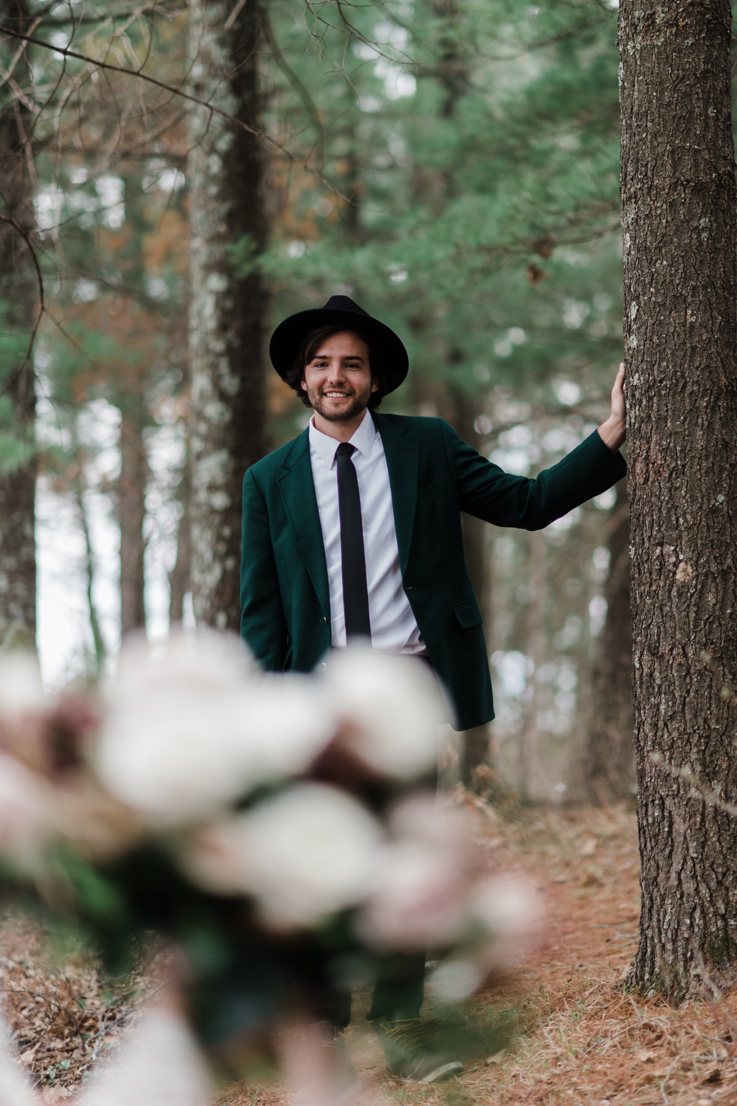 Groom wearing a green blazer and black fedora leaning on a tree in the woods.
