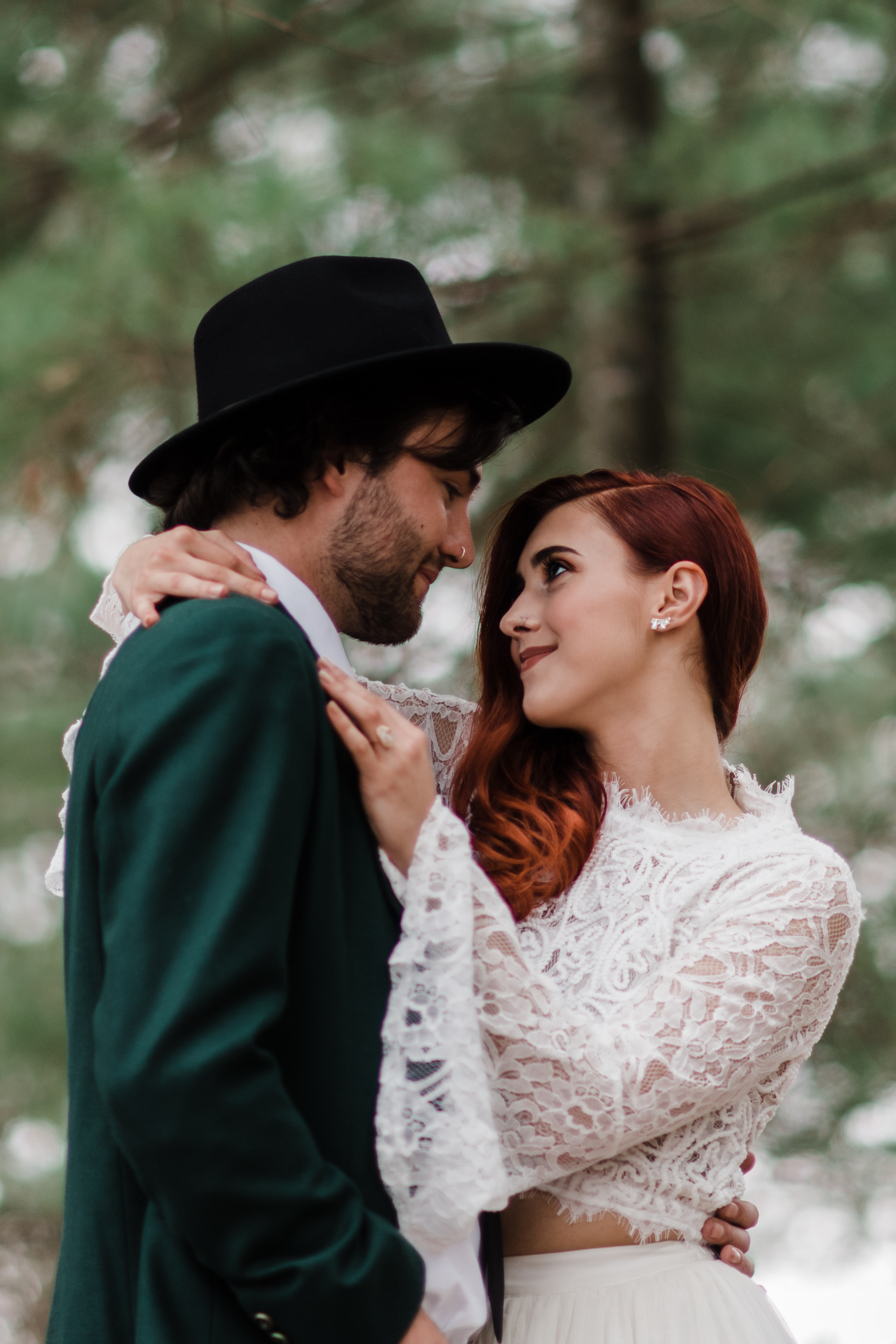 Bride in lace and beaded crop top with arms wrapped around groom in green jacket and black fedora and gazing into his eyes.