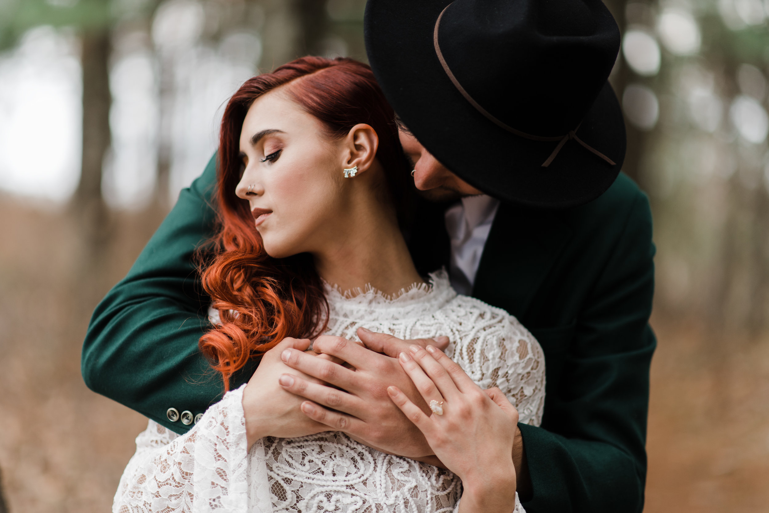 Groom in green jacket and black fedora with arms wrapped around bride in lace and beaded crop top.