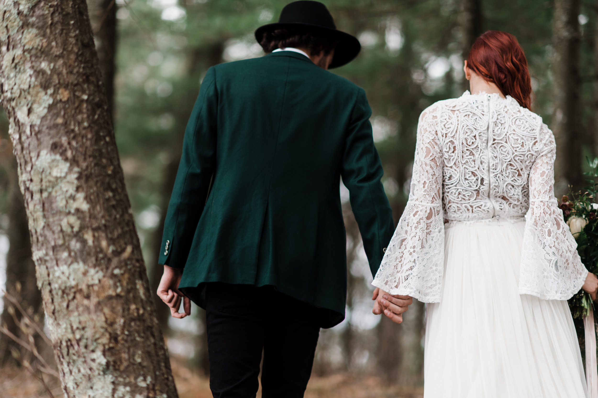 Groom in green jacket and black fedora walking and holding hands with bride in lace and beaded crop top and flowing skirt.