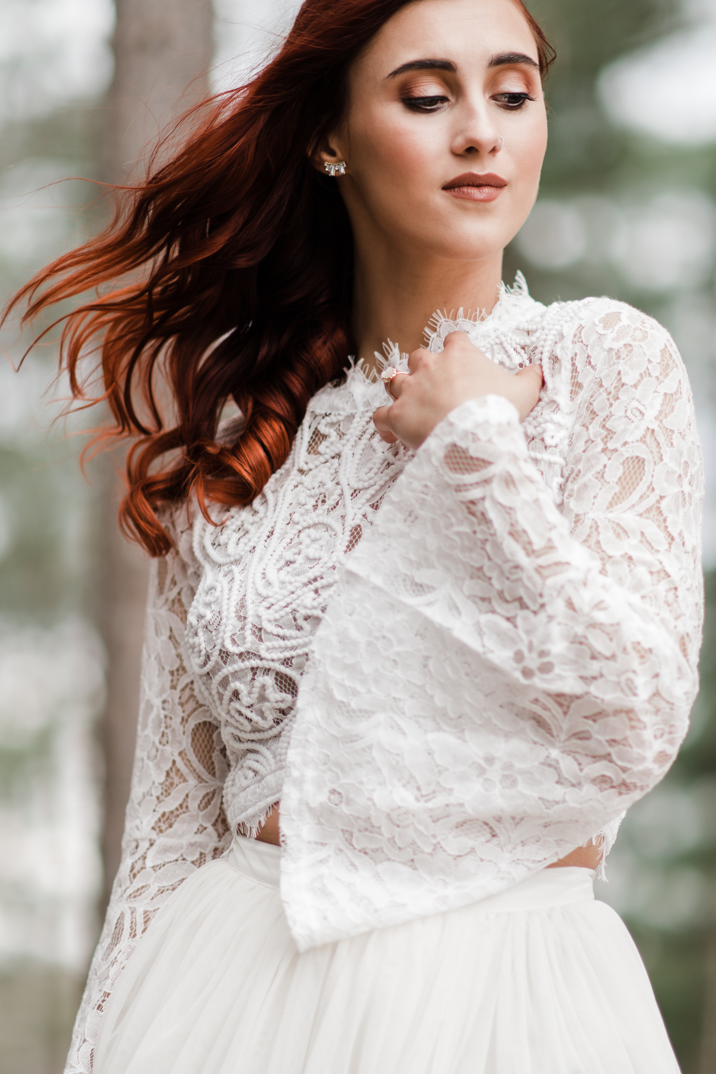 Bride in lace and beaded crop top with red curly hair blowing in the wind and hand softly on her heart and looking down over her shoulder.