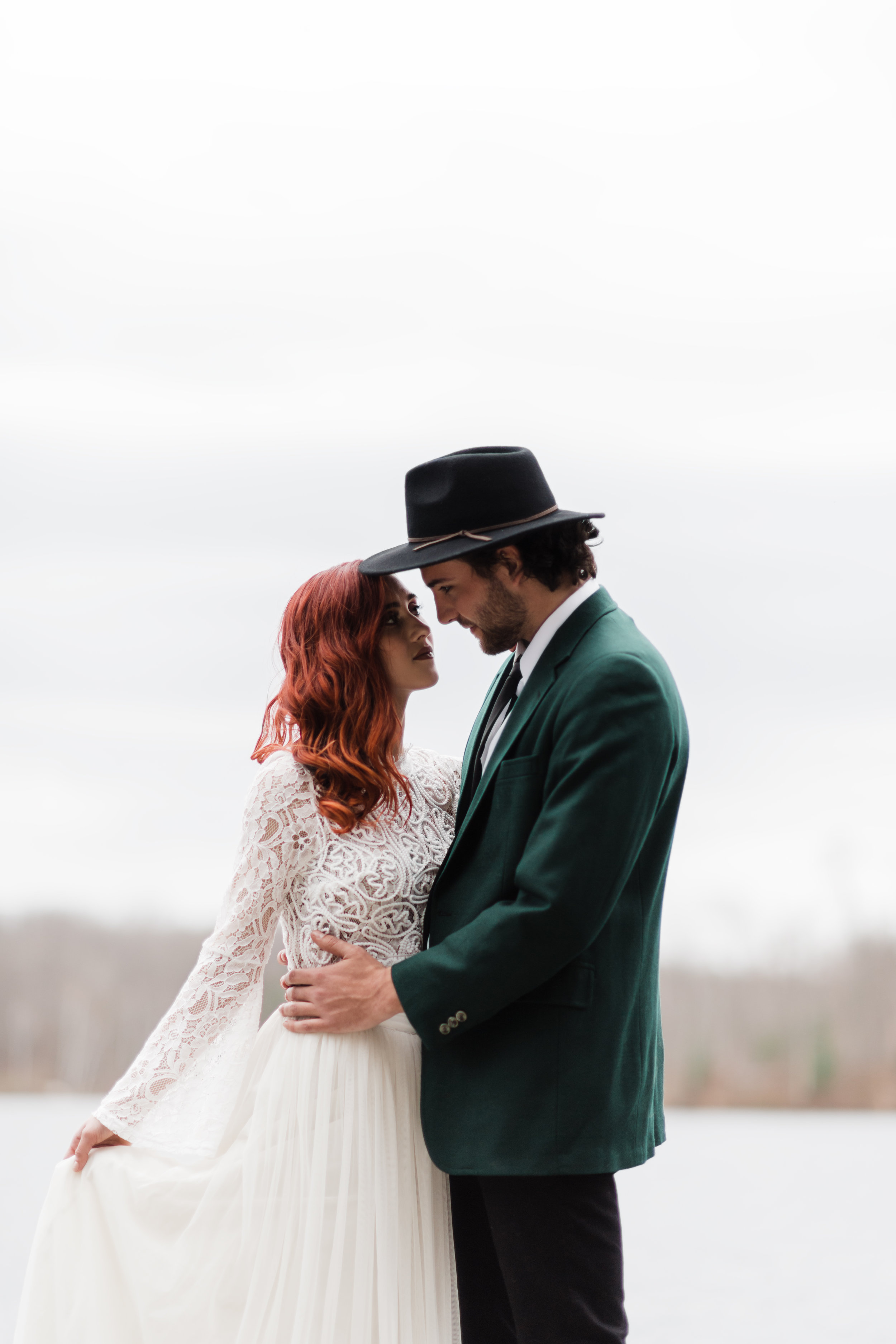 Bride in lace and beaded crop top and hand holding flowing skirt gazing into the eyes of groom in green jacket and black fedora.