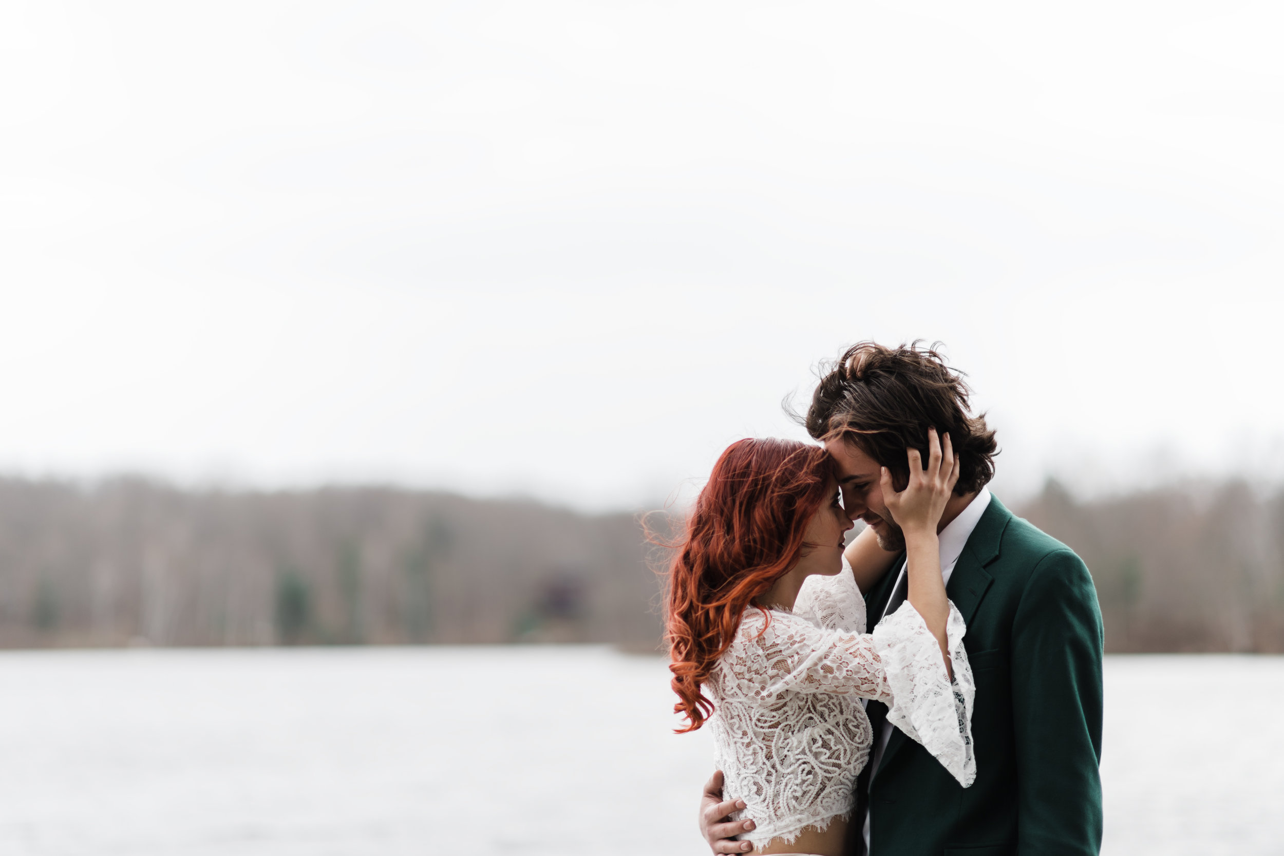 Bride with curly red hair in lace and beaded crop top running hands through groom's hair.