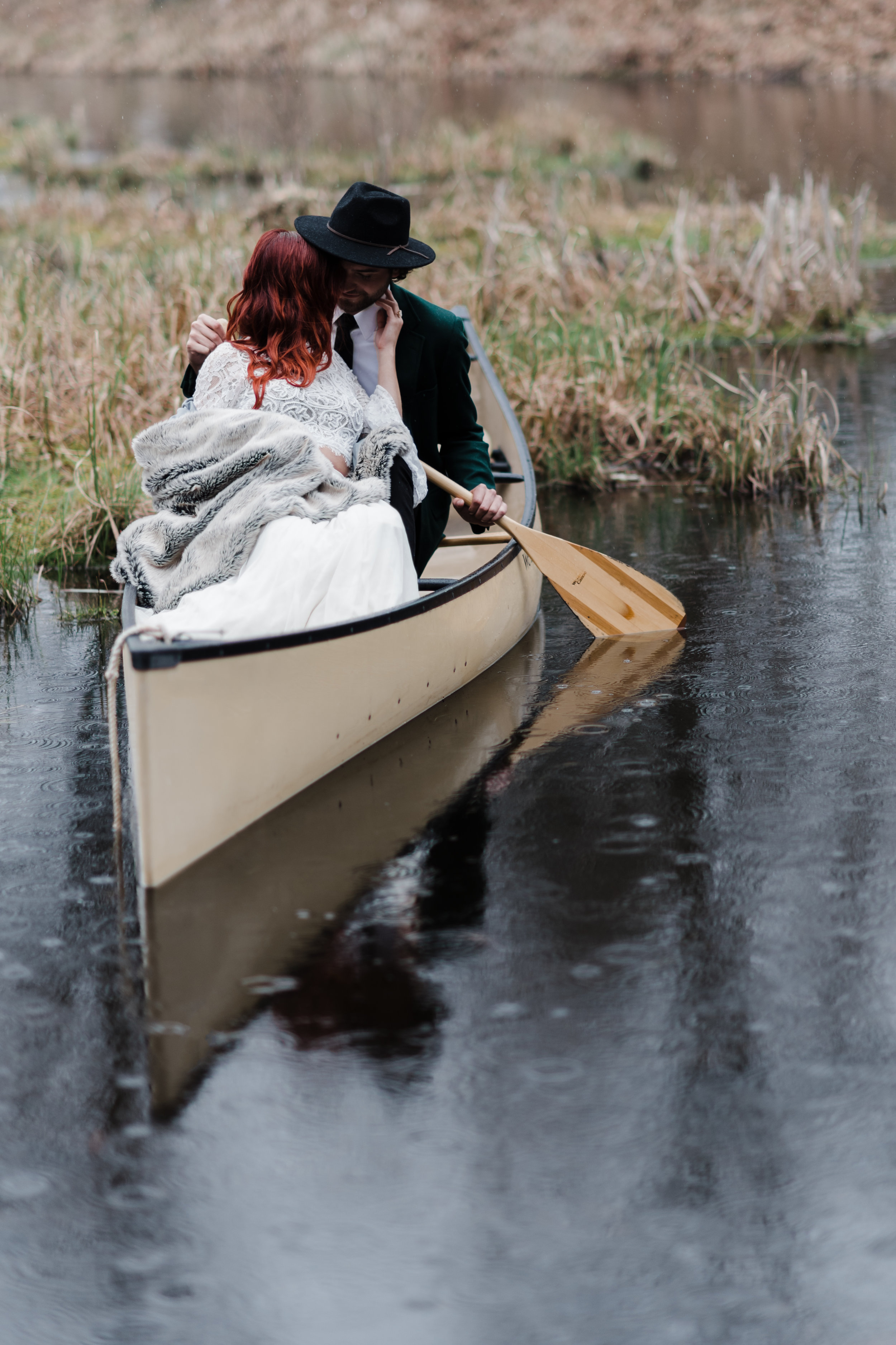 Bride in lace and beaded crop top and flowing skirt wrapped in a fuzzy blanket leaning on groom in green jacket and black fedora rowing a canoe.