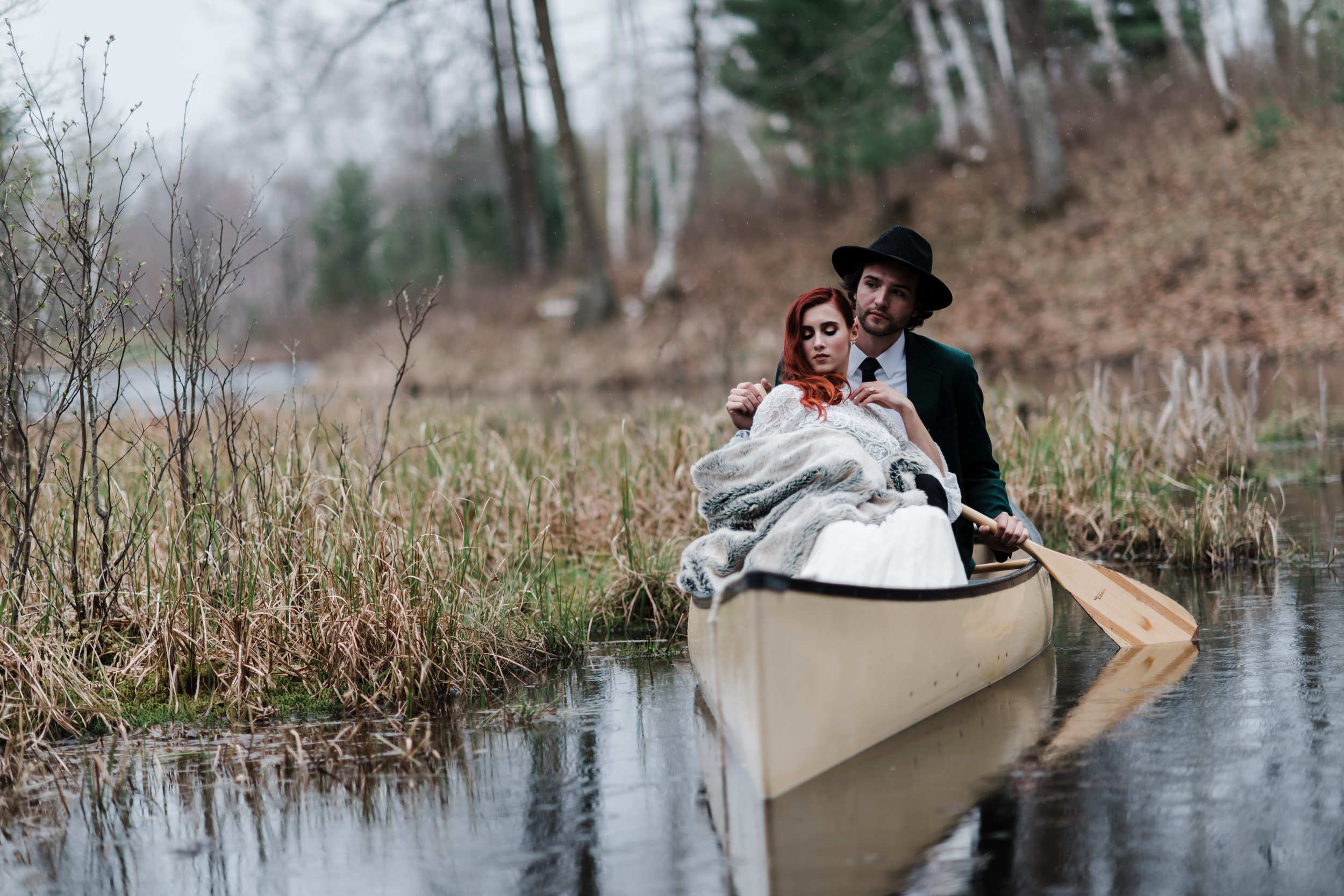 Bride in lace and beaded crop top wrapped in fuzzy blanket and groom in green jacket and black fedora in a canoe.