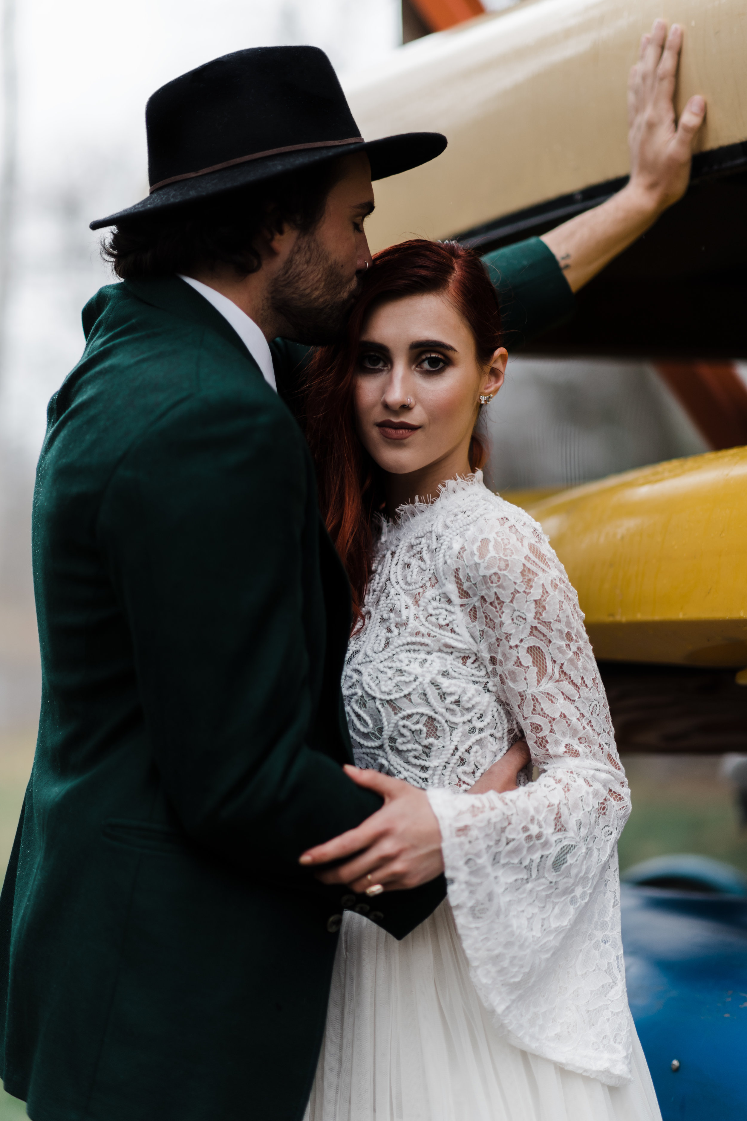 Groom in green jacket and black fedora kissing forehead of bride in lace and beaded crop top and flowing skirt in front of colorful canoes.