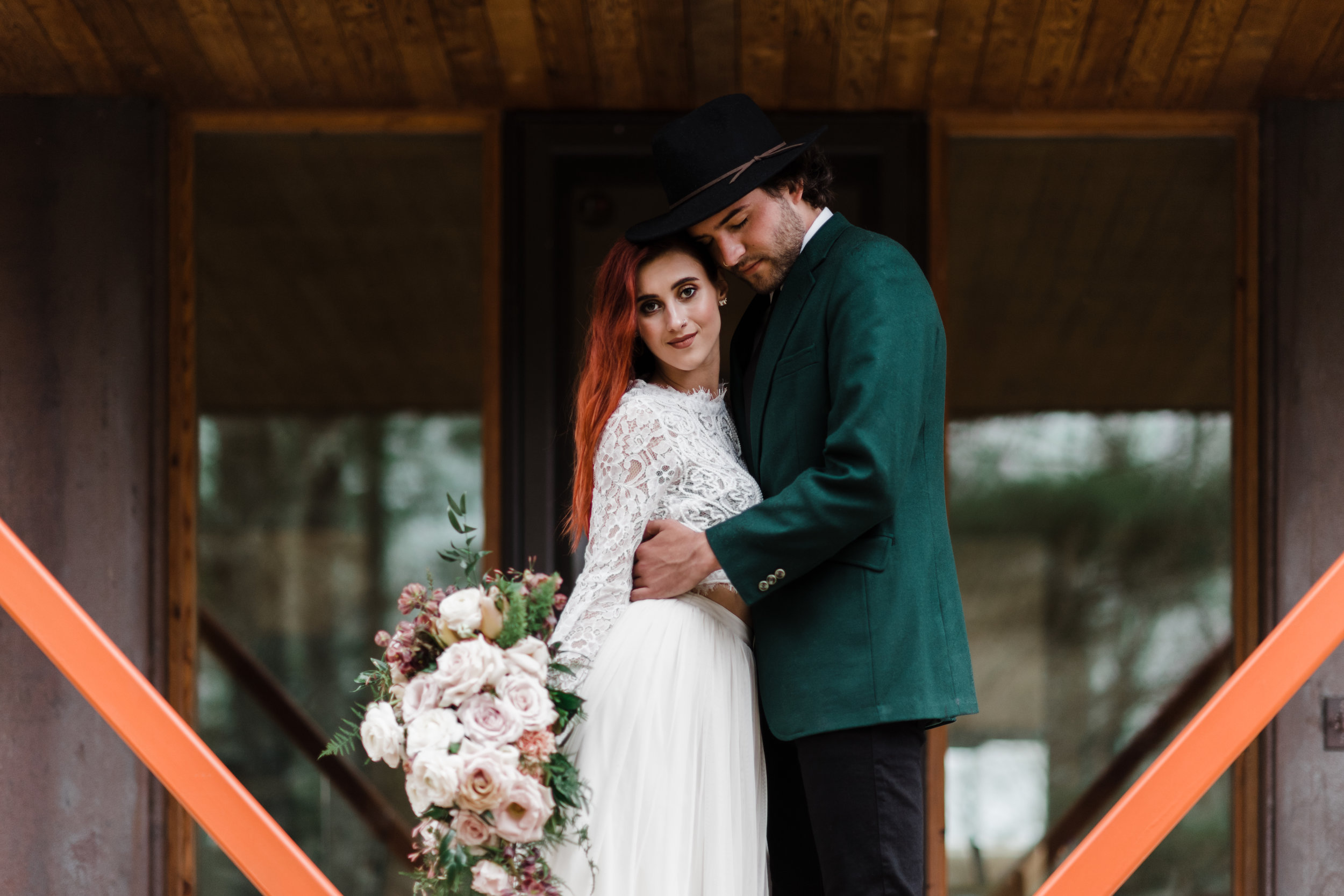 Groom in green jacket and black fedora and bride in lace and beaded crop top and flowing skirt in front of door with orange beams.